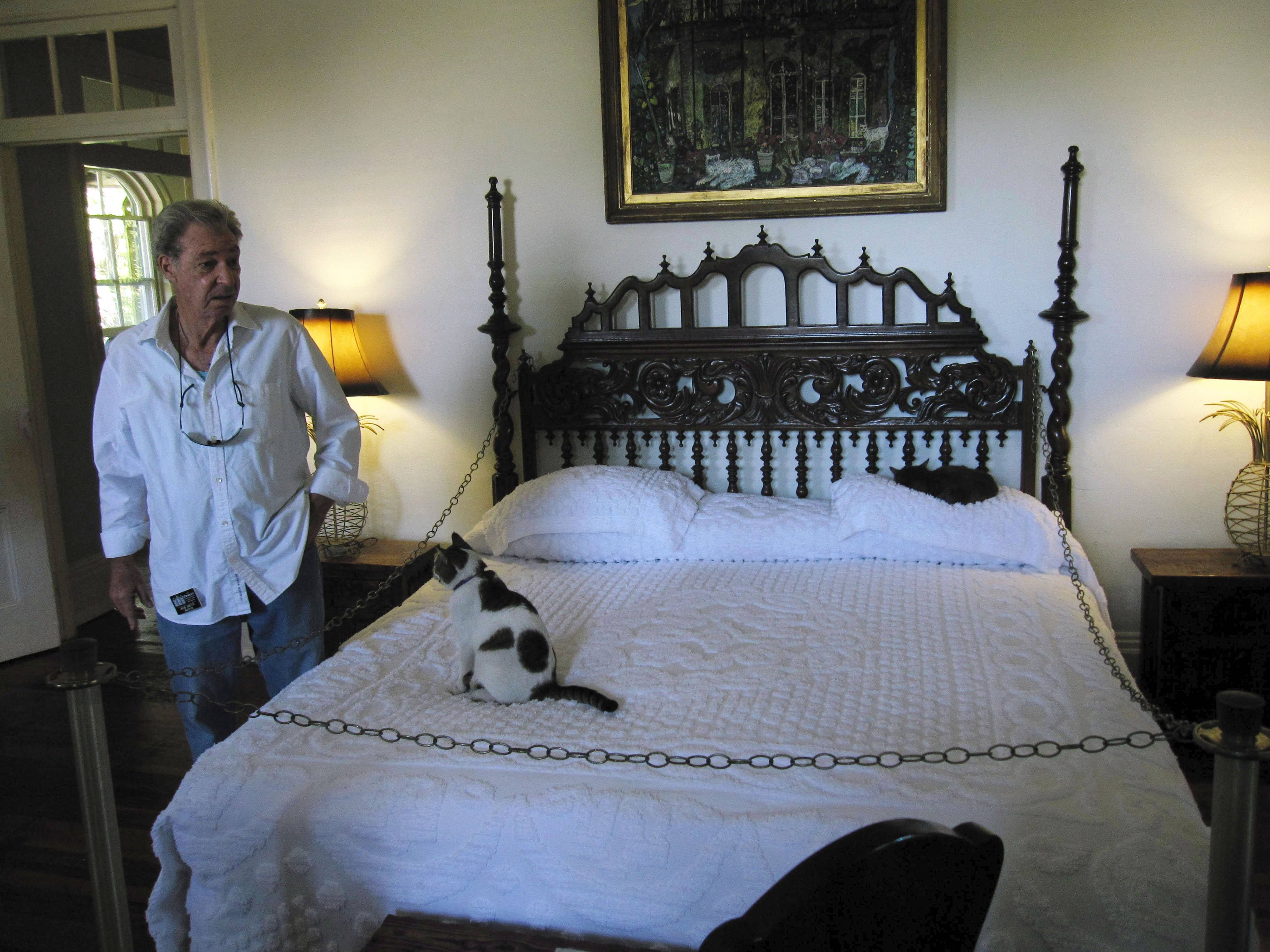 Tour guide Bob Smith at the Hemingway Home in Key West, Fla., comes across one of the home's cats, named Fats Waller. The home belonged to the late author Ernest Hemingway, who had a six-toed cat, and many of the 40 to 50 cats who reside there today have the polydactyl gene for an extra toe.