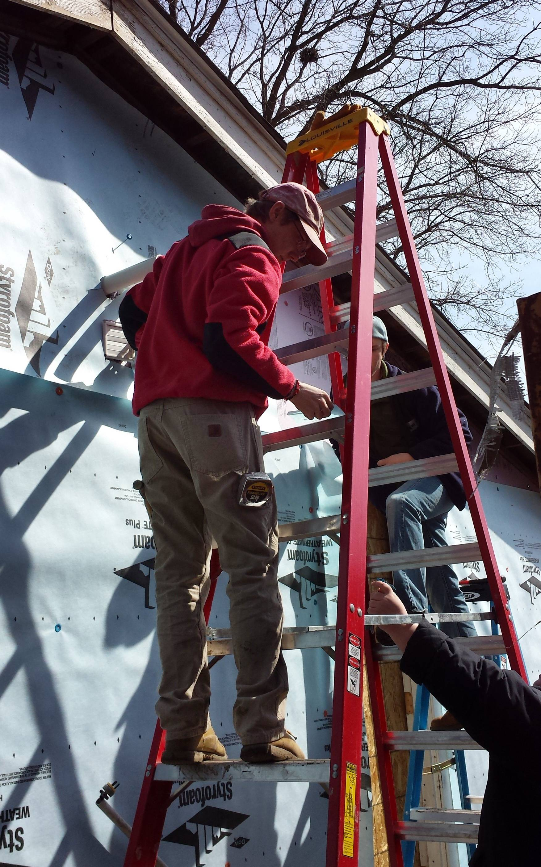 Jason Bauer helps prepare the outside of a Habitat for Humanity home in Carpentersville for siding. Bauer is among 10 Elgin Community College students participating in the Alternative Spring Break program.