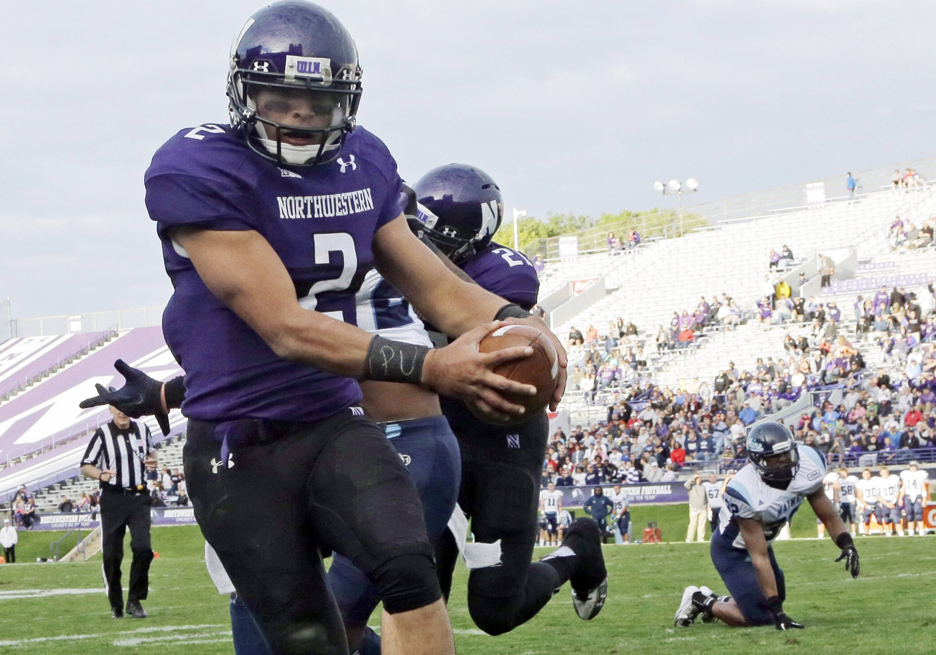 "In this photo from Sept. 21, 2013, Northwestern quarterback Kain Colter, wears APU for ""All Players United"" on wrist tape as he scores a touchdown during an NCAA college football game against Maine in Evanston. The decision to allow Northwestern football players to unionize raises an array of questions for college sports. Among them, state schools vs. public schools, powerhouse programs vs. smaller colleges."