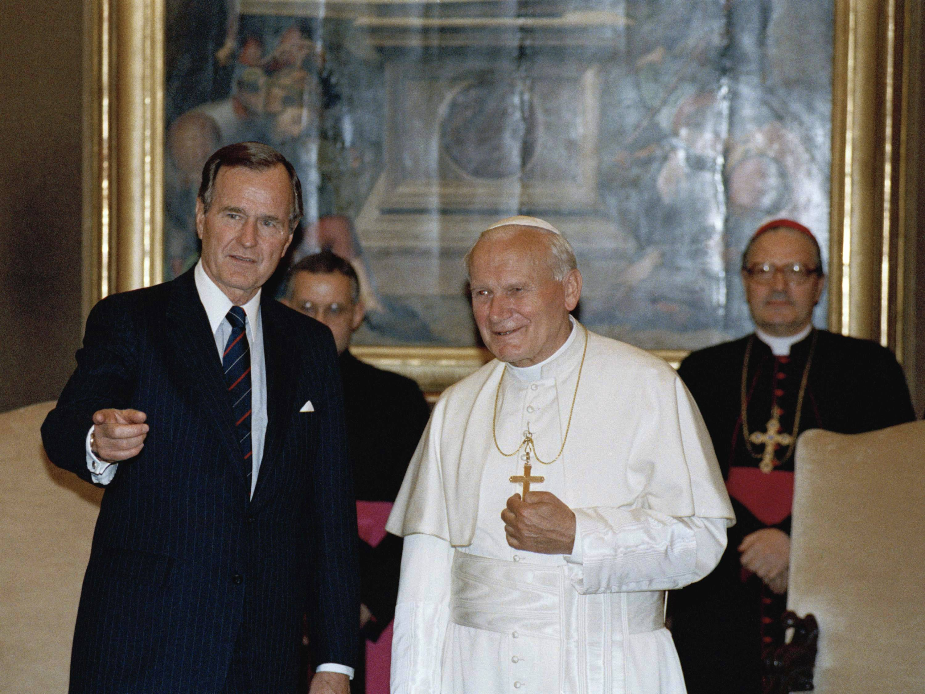 President George H.W. Bush gestures while standing with Pope John Paul II in the papal library at the Vatican.