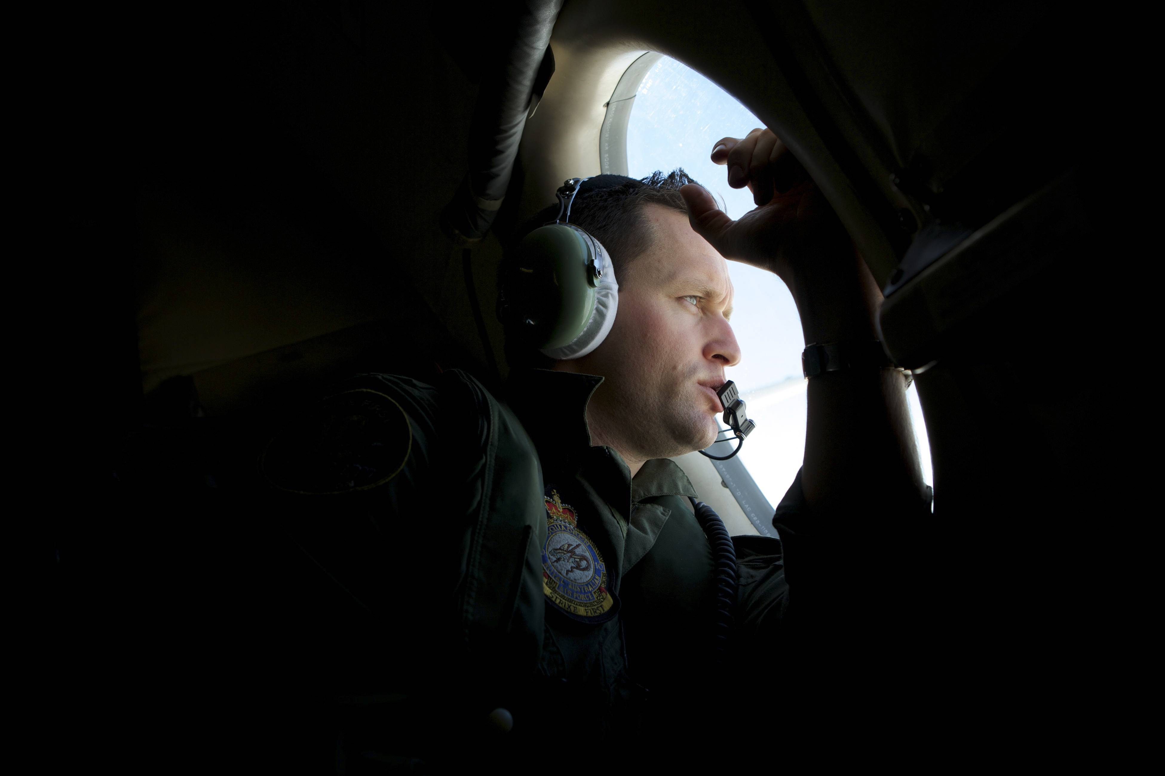 A crew member of an Royal Australian Air Force AP-3C Orion patrol plane, looks out of his observation window whilst searching for the missing Malaysia Airlines Flight MH370 over the India