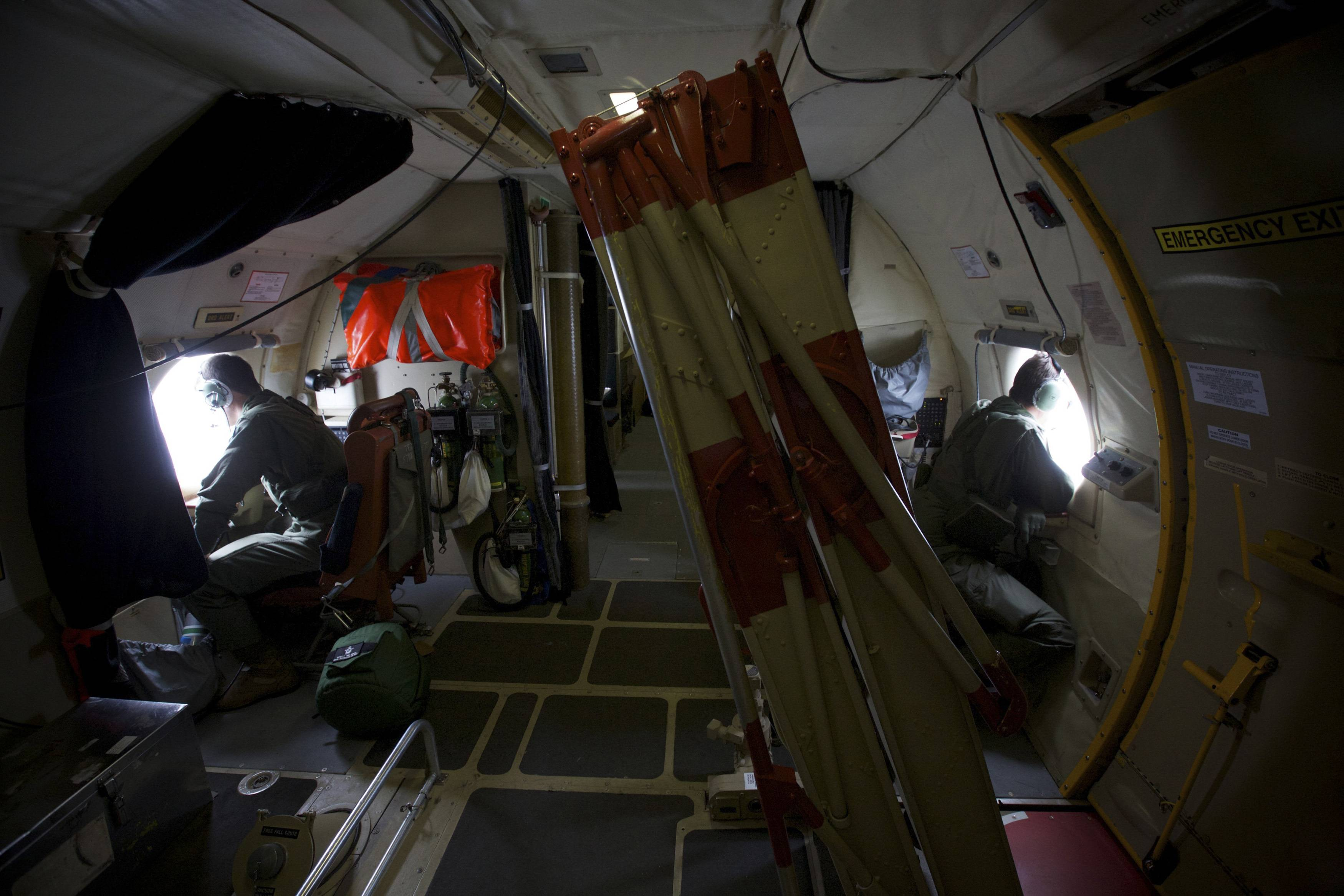 There are two spotters on either side of the aircraft. They rest their elbows on a padded shelf, their binoculars sitting at arm's reach. A small pocket near each window contains safety manuals, paperwork and a handful of barf bags. On at least one particularly bumpy flight, the crew had to use them.
