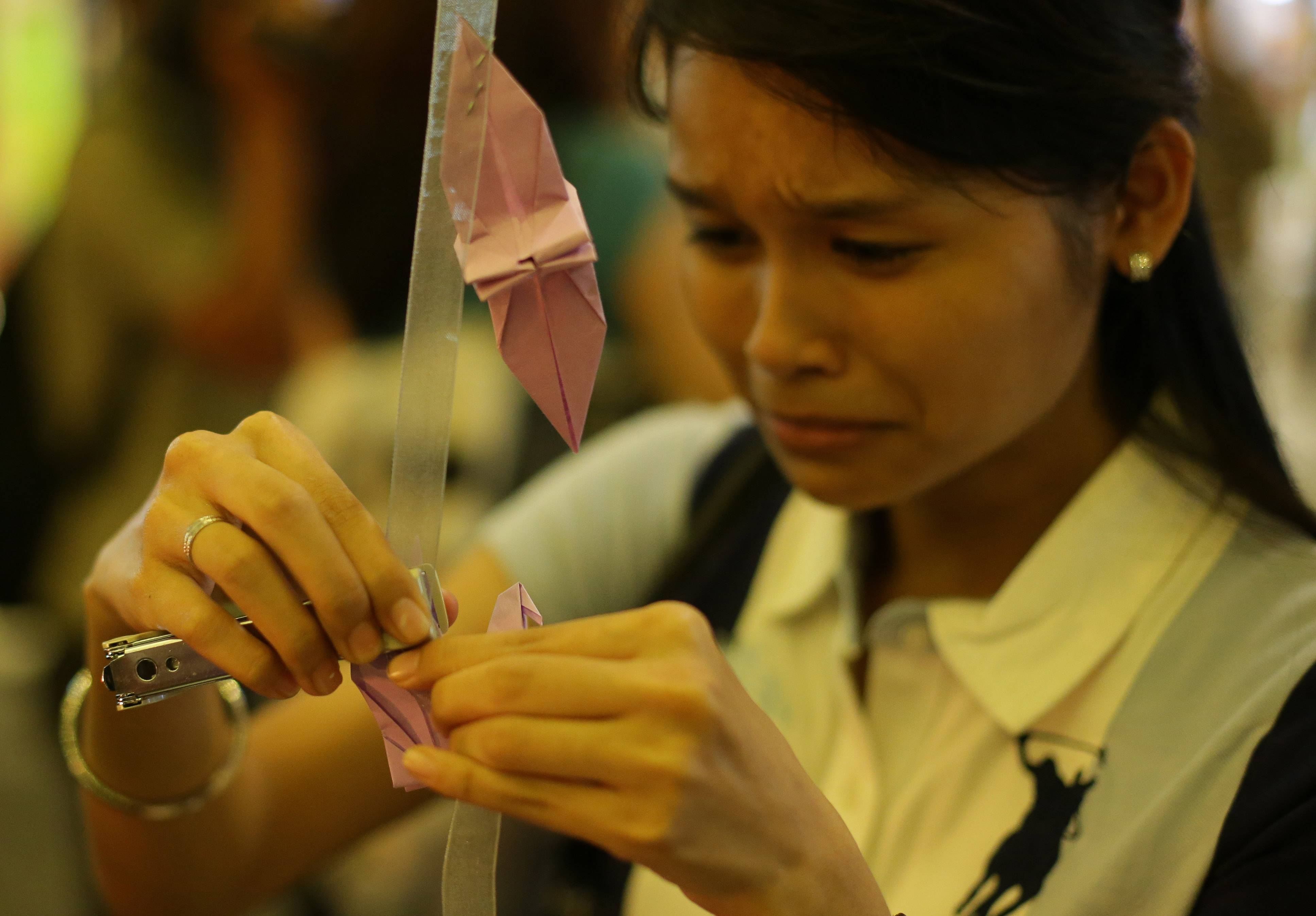 A woman breaks into tears as she places a paper crane as a symbol for hope and healing during a ceremony in memory of passengers on board the missing Malaysia Airlines Flight MH370 in Kuala Lumpur, Malaysia, Thursday.