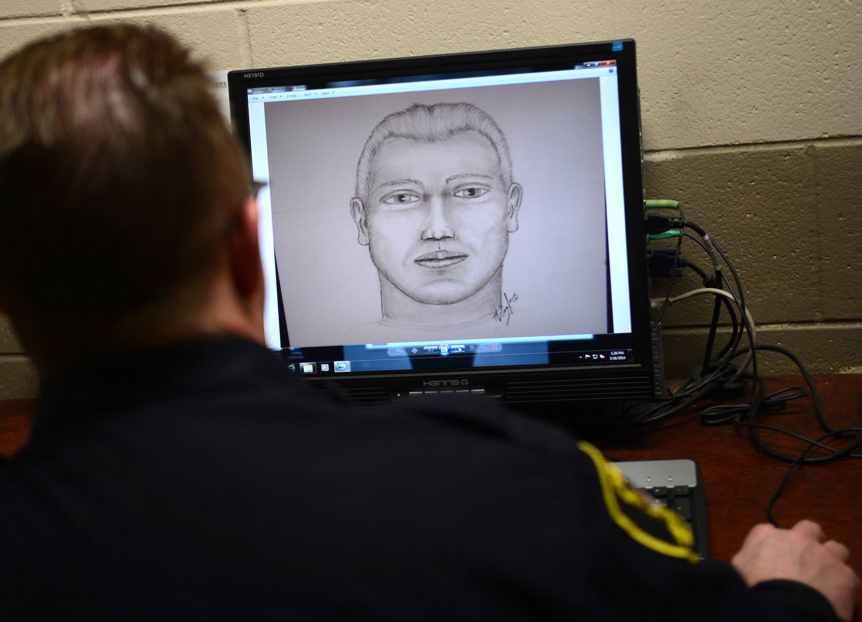 Elgin Police officer Mike Gough shows one of the many sketches he's done in his years as a sketch artist.