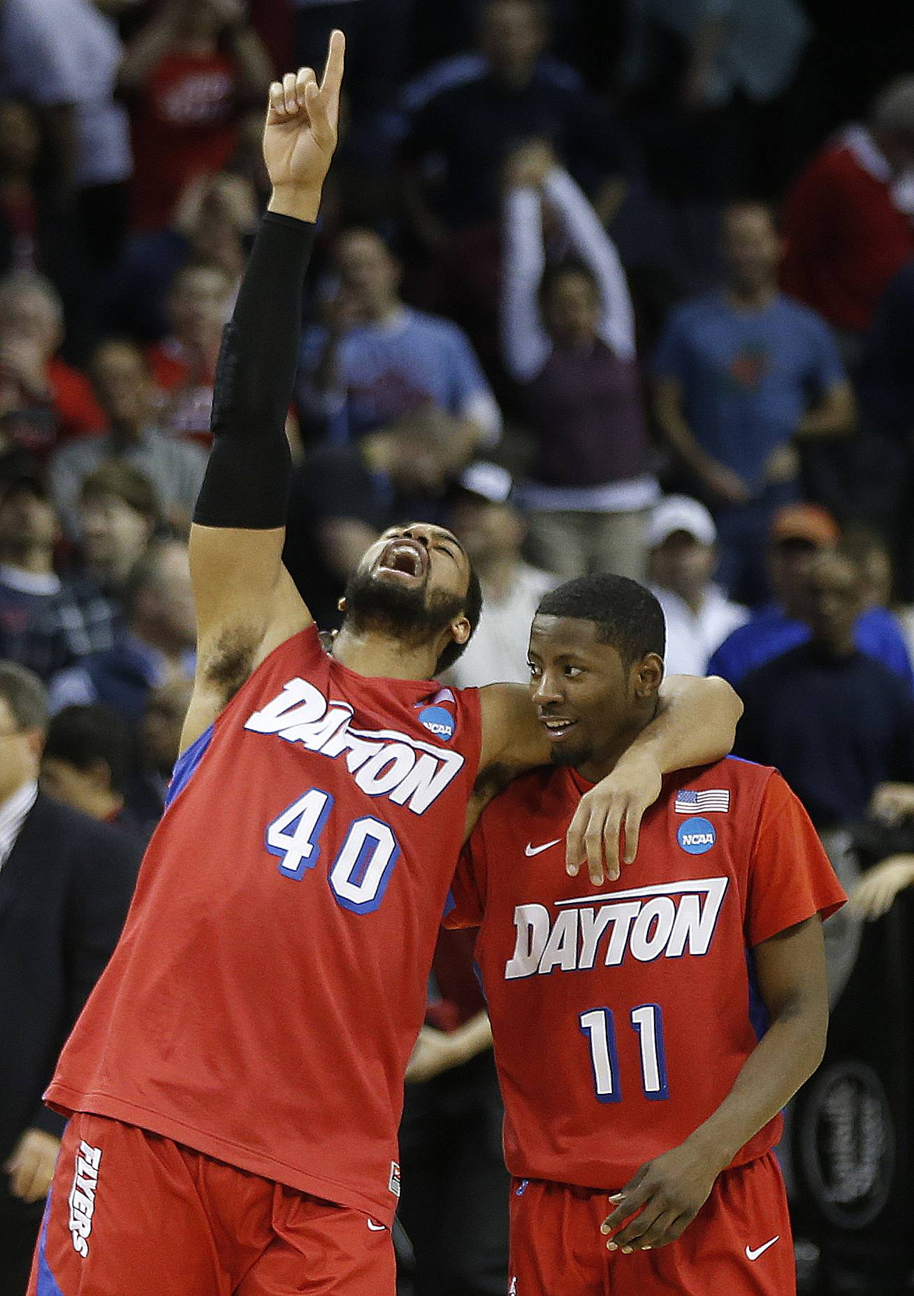 Dayton's Devon Scott (40) and Scoochie Smith (11) celebrate after the second half in a regional semifinal game against Stanford at the NCAA college basketball tournament, Thursday, March 27, 2014, in Memphis, Tenn. Dayton won 82-72.