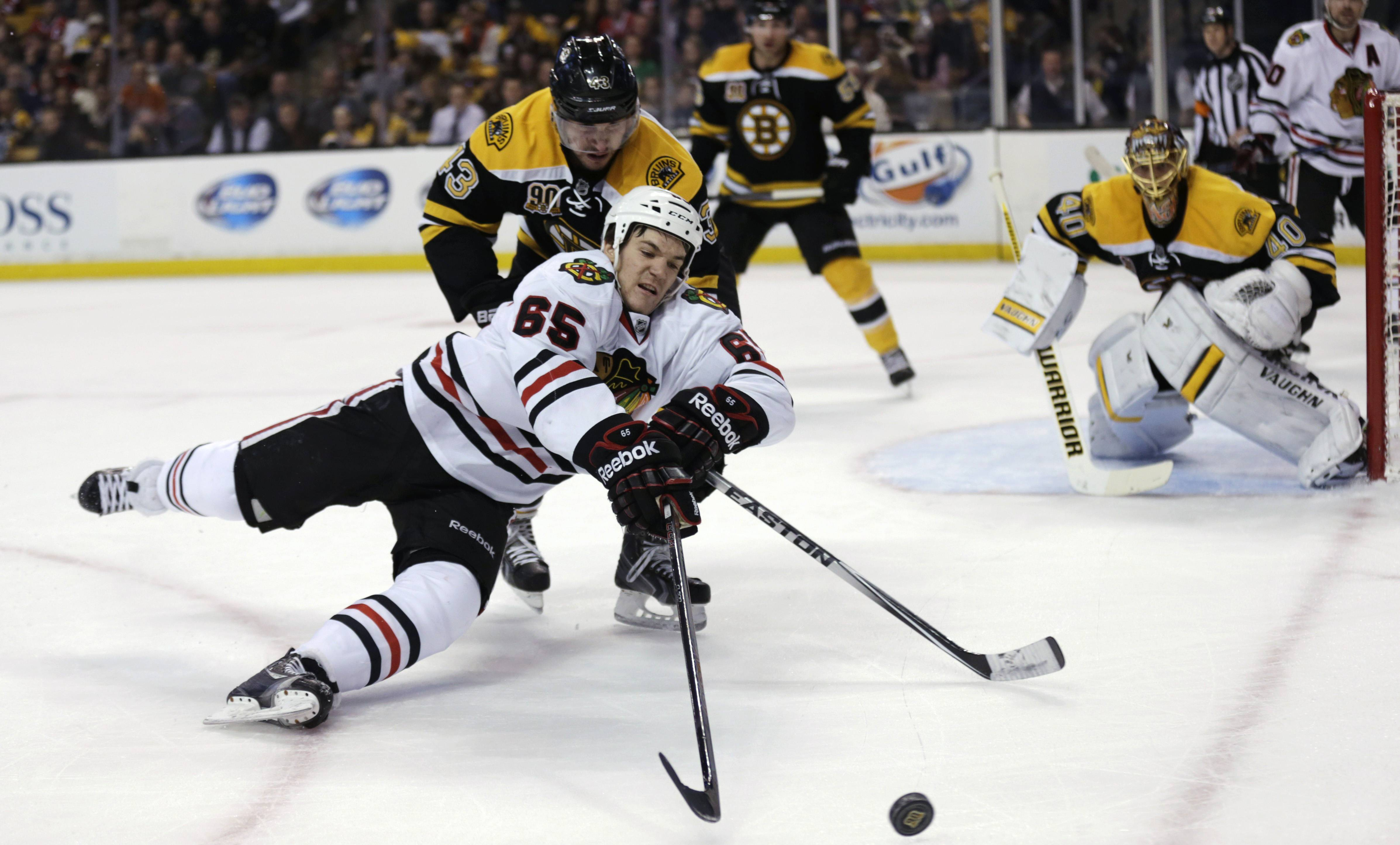 Blackhawks forward Andrew Shaw (65) is knocked to the ice by Boston Bruins defenseman Matt Bartkowski (43) as they chase the puck during the first period of an NHL hockey game, Thursday, March 27, 2014, in Boston.