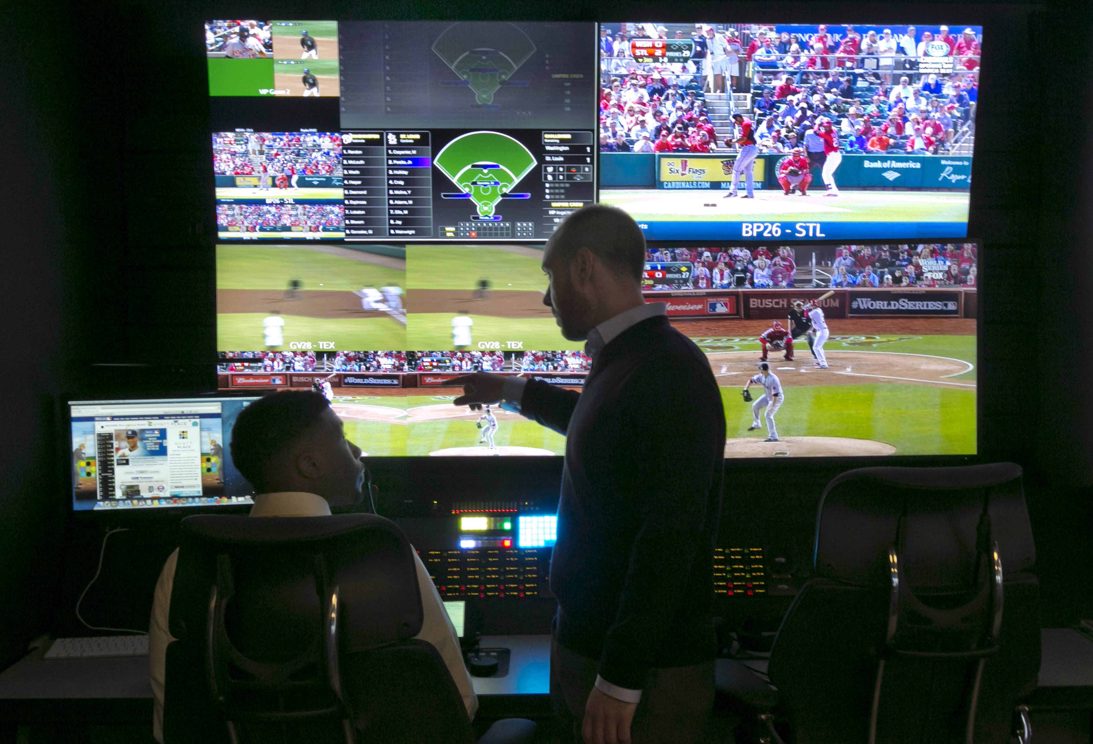 Two technicians work in a booth during a preview of Major League Baseball's Replay Operations Center, in New York, Wednesday, March 26, 2014. Less than a week before most teams open, MLB is working on the unveiling of its new instant replay system, which it hopes will vastly reduce incorrect calls by umpires.