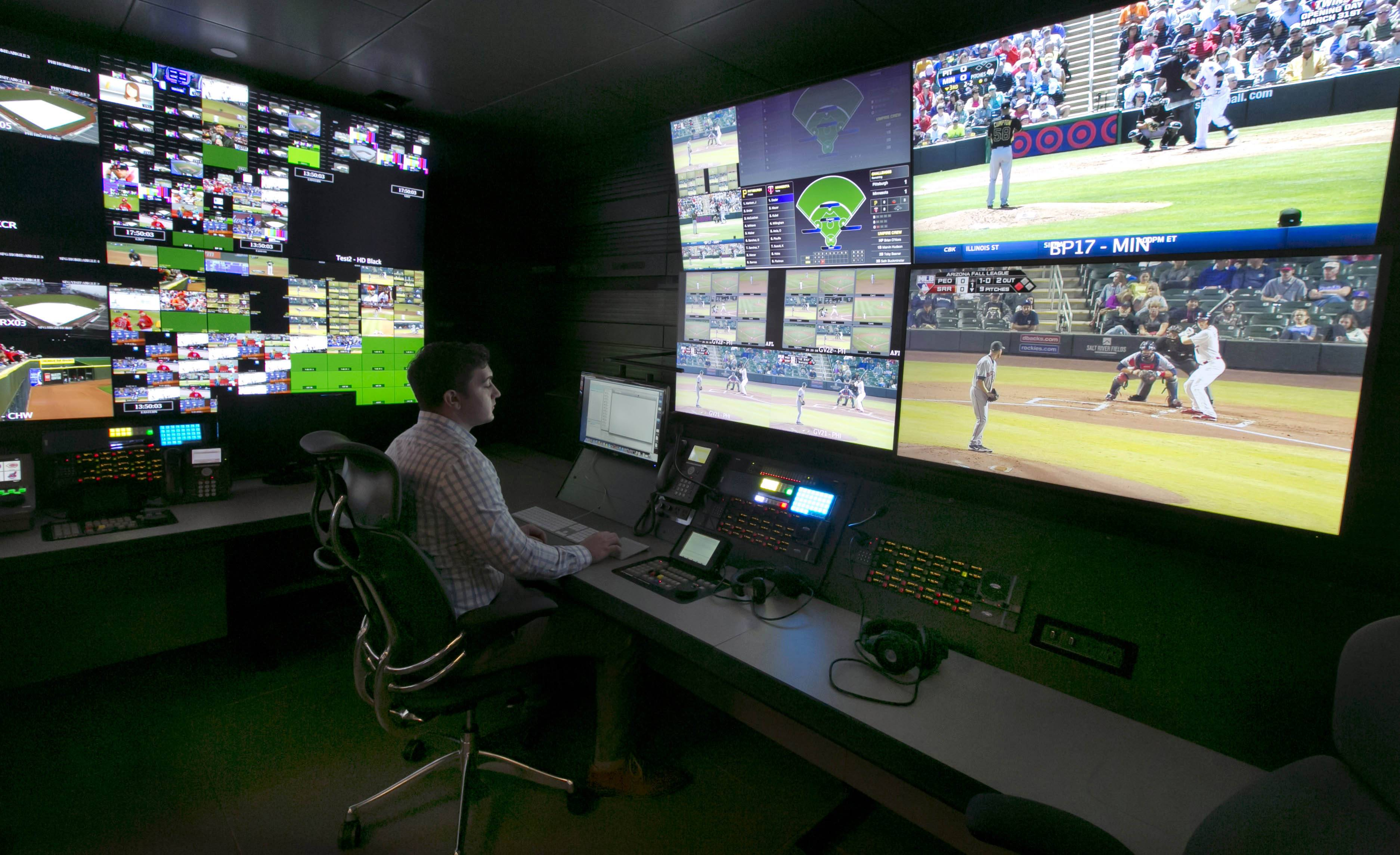 A technician works in front of a bank of television screens during a preview of Major League Baseball's Replay Operations Center, in New York, Wednesday, March 26, 2014.  Less than a week before most teams open, MLB is working on the unveiling of its new instant replay system, which it hopes will vastly reduce incorrect calls by umpires.