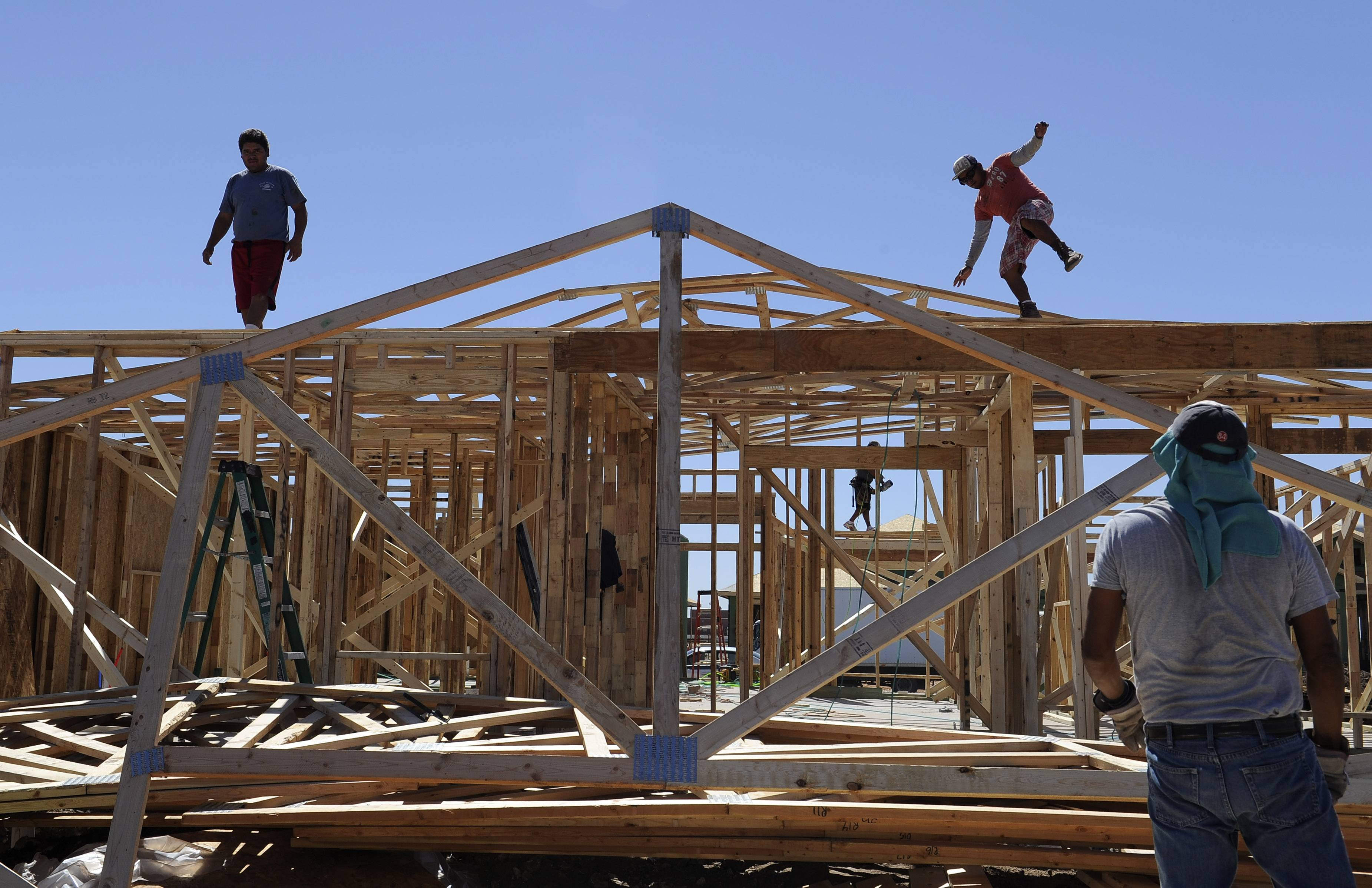 A man steadies himself as he and others work on framing new houses, in Odessa, Texas. America's energy boom is fueling population growth west of the Mississippi River.