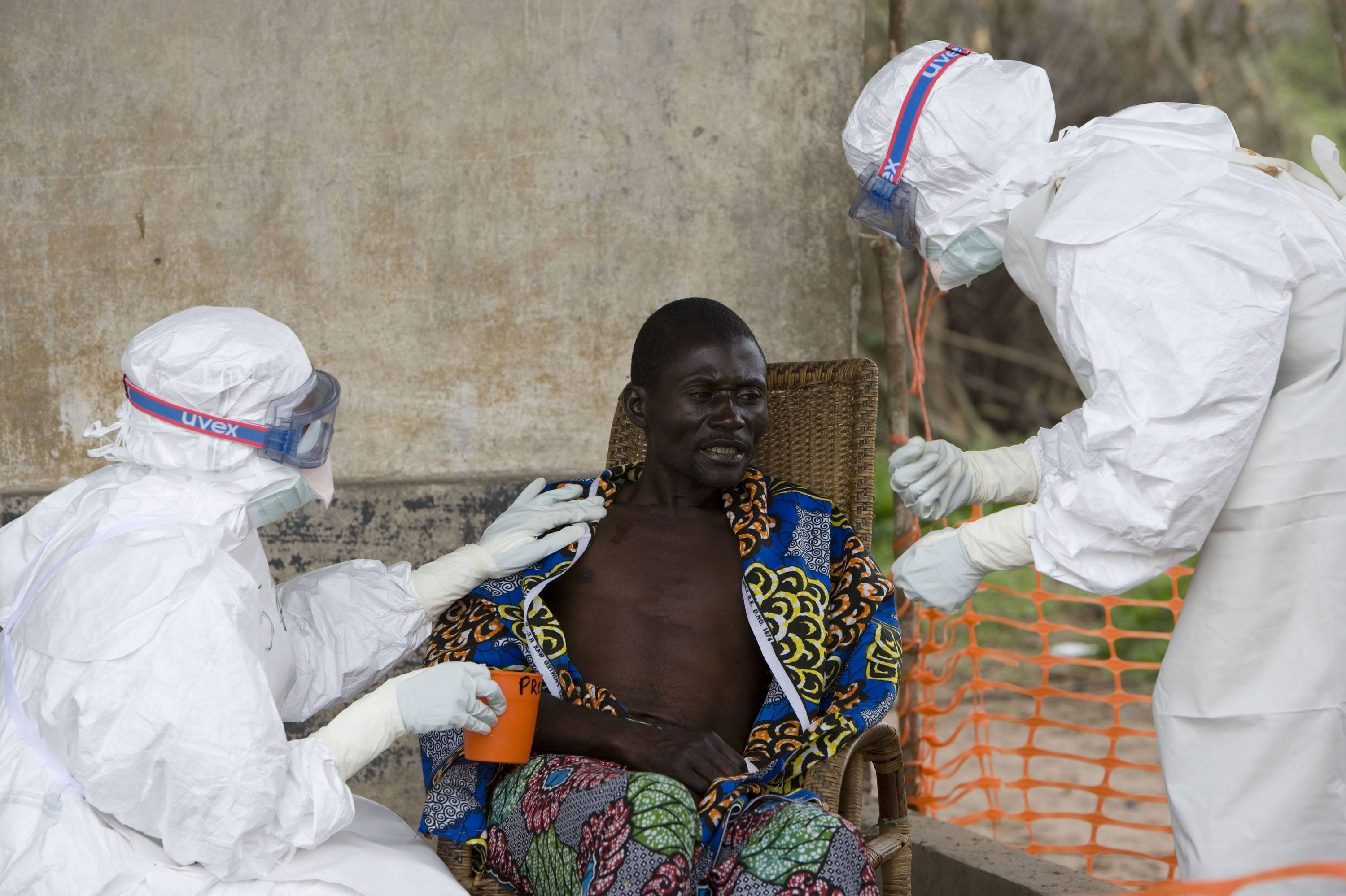 A 43 year old Congolese patient, center, who has been confirmed to have Ebola hemorrhagic fever, following laboratory tests, is comforted by Doctors without Borders personnel.