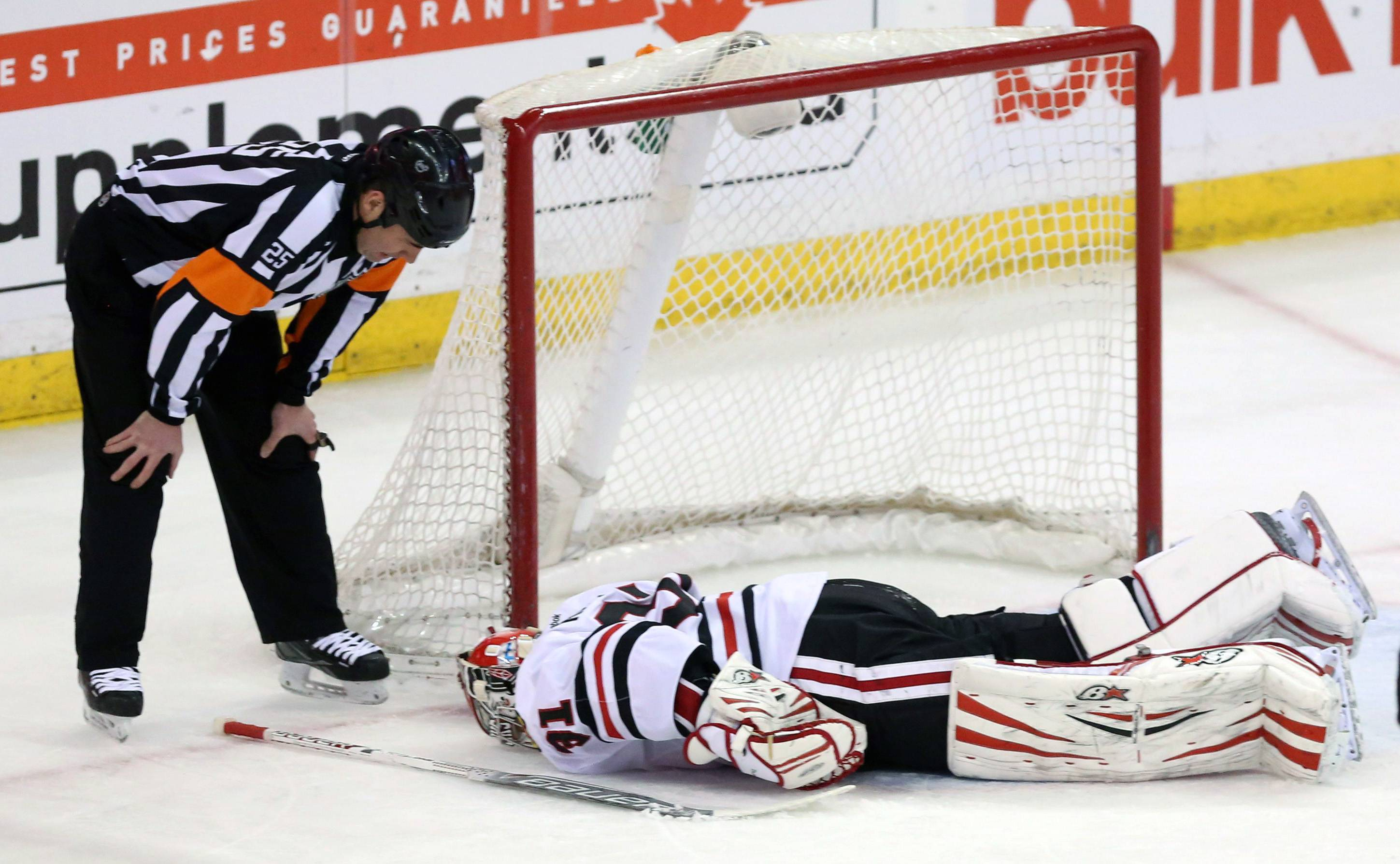 Chicago Blackhawks goaltender Antti Raanta (31), of Finland, lies injured near his net as referee Marc Joannette looks at him during first-period NHL hockey game action against the Ottawa Senators in Ottawa, Ontario, Friday, March 28, 2014. Raanta stayed in the game.