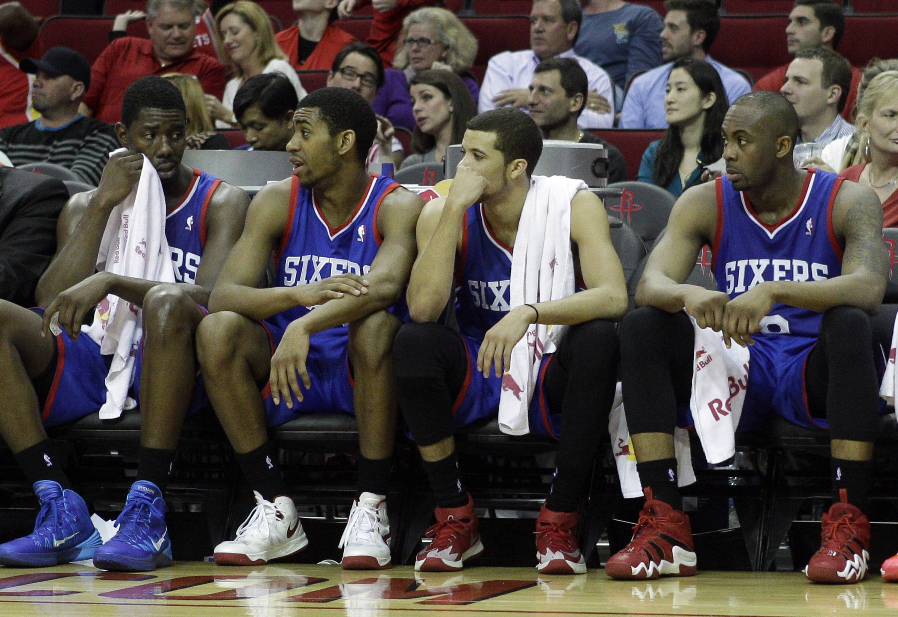From left to right, Philadelphia 76ers' Henry Sims, Hollis Thompson, Michael Carter-Williams and James Anderson watch the final minutes during the second half of an NBA basketball game against the Houston Rockets, Thursday, March 27, 2014, in Houston. Houston won 120-98. (AP Photo/Bob Levey)