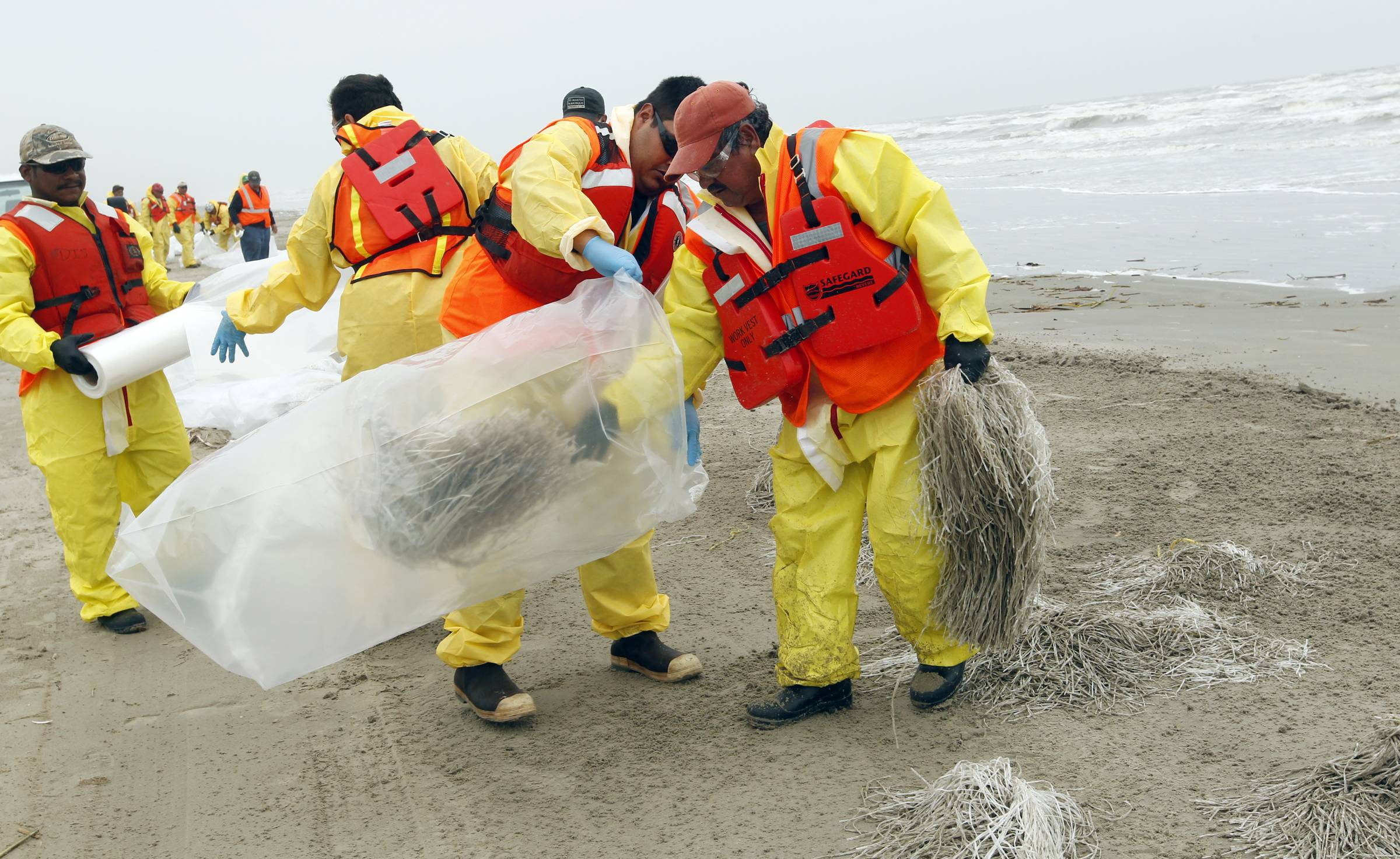 Oil spill response crews remove oil absorbent material placed on the beach between Stewart Beach and East Beach in Galveston on Thursday March 27, 2014. The material was placed on the stretch of beach as a precaution as cleanup continues after 168,000 gallons of heavy fuel oil spilled in to Galveston Bay on Saturday.
