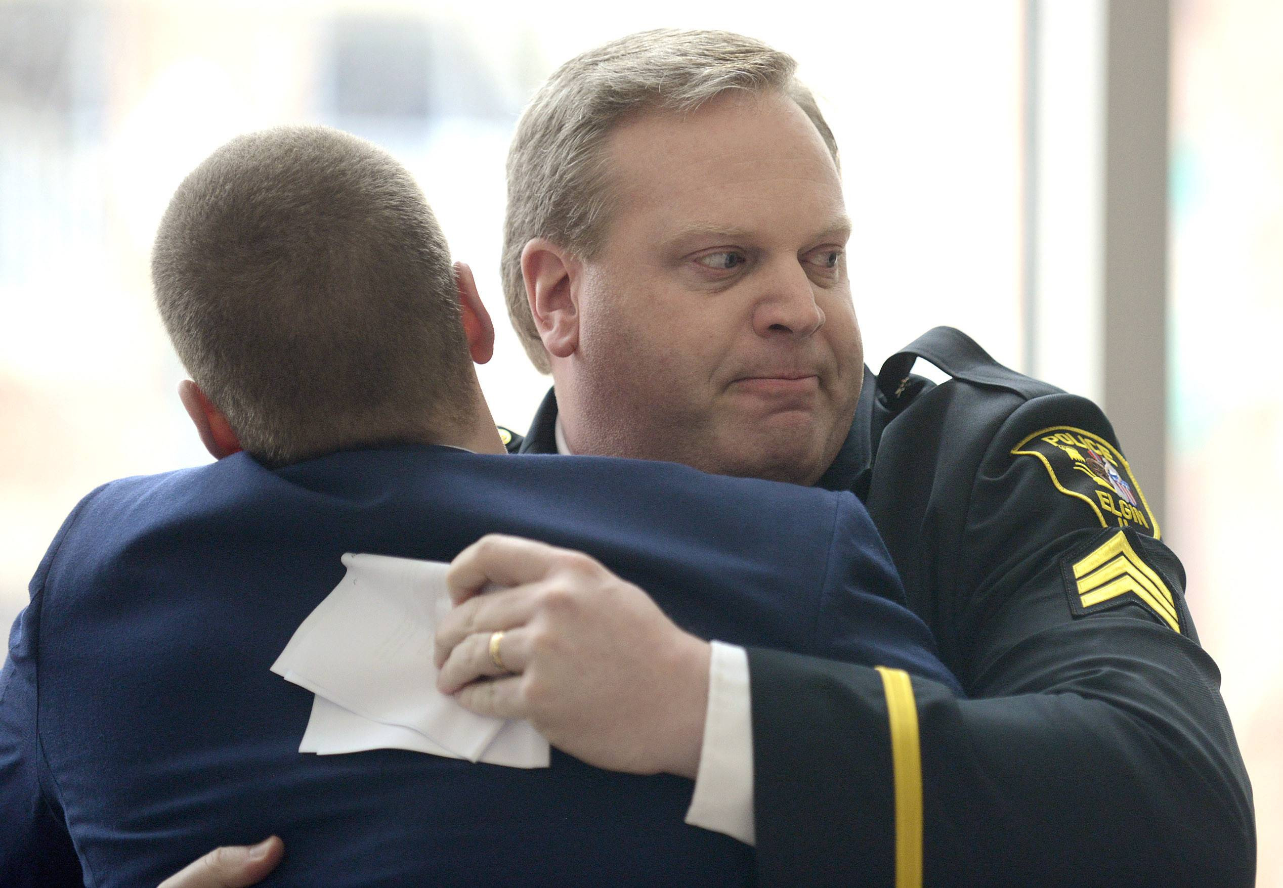 Retiring Elgin Police Sgt. Don Thiel gets a hug from his son, Danny, after giving his retirement speech Friday. Danny, 21, is in the Air Force, based in New Jersey, and flew in for the ceremony.