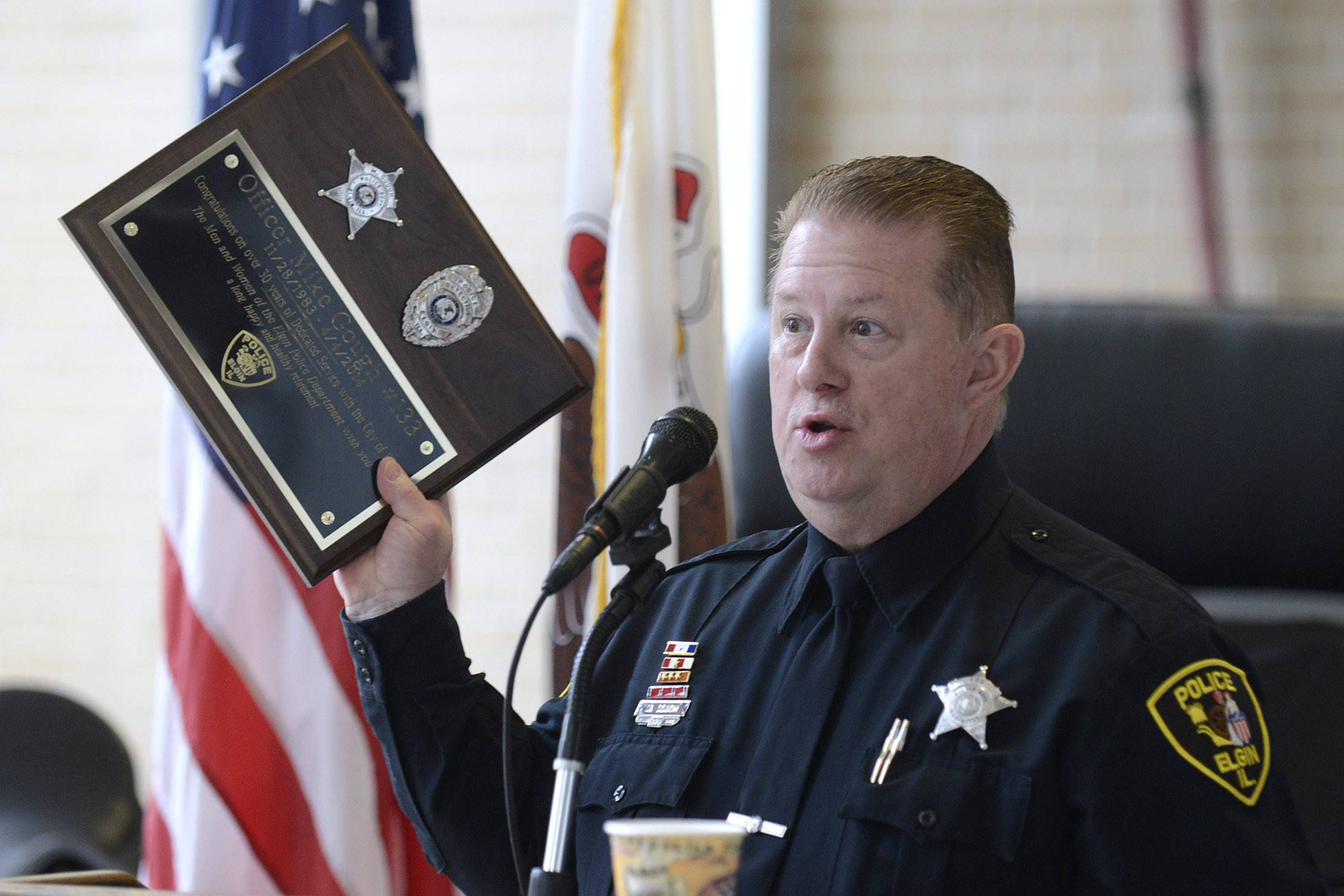 "Elgin Police Officer Mike Gough, a sketch artist, holds up his retirement plaque, telling the crowd gathered ""This is for you"" at the Elgin Police Department headquarters Friday."