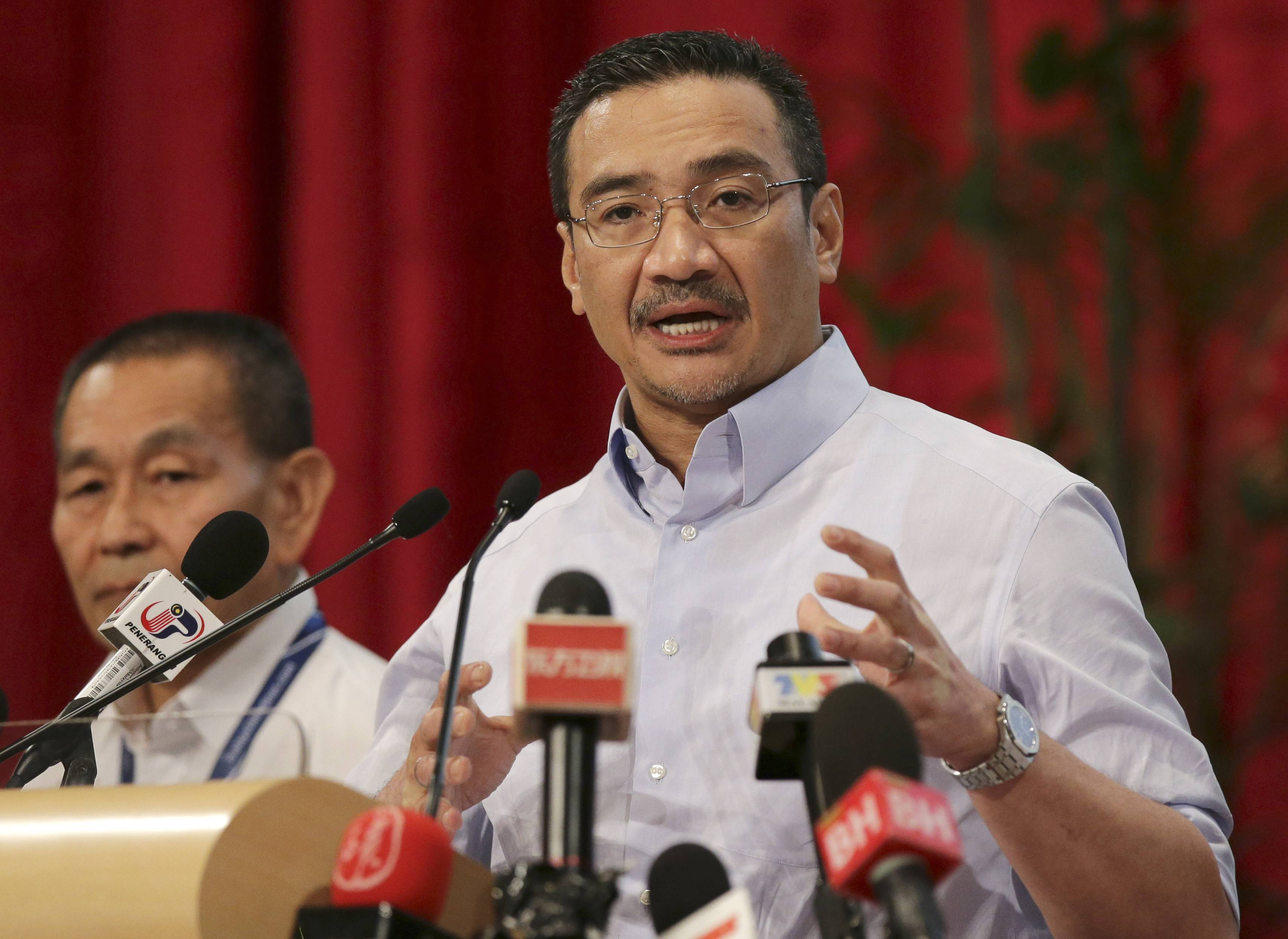 Malaysia's acting Transport Minister Hishammuddin Hussein, right, answers a reporter's question.