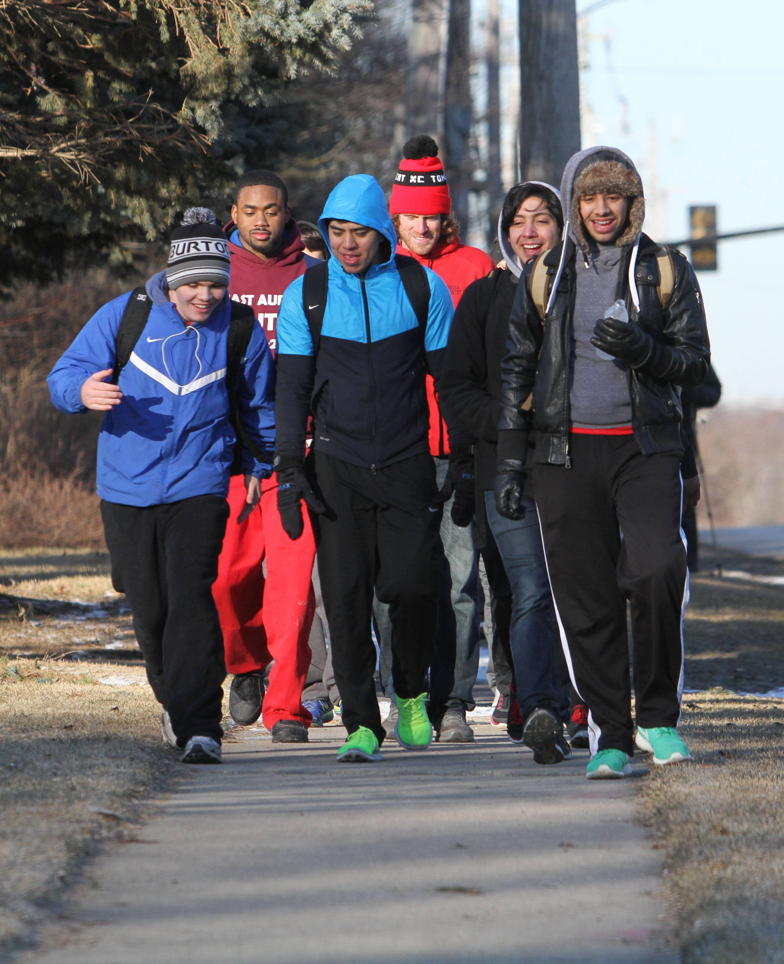 "A group of students from East Aurora High School leads the way Wednesday morning in the ""Tomcats Journey to Remember,"" which took them down 38 miles of sidewalks between their school and Soldier Field in Chicago. Making it to Naperville by 8 a.m., the students had completed about nine miles of their journey."