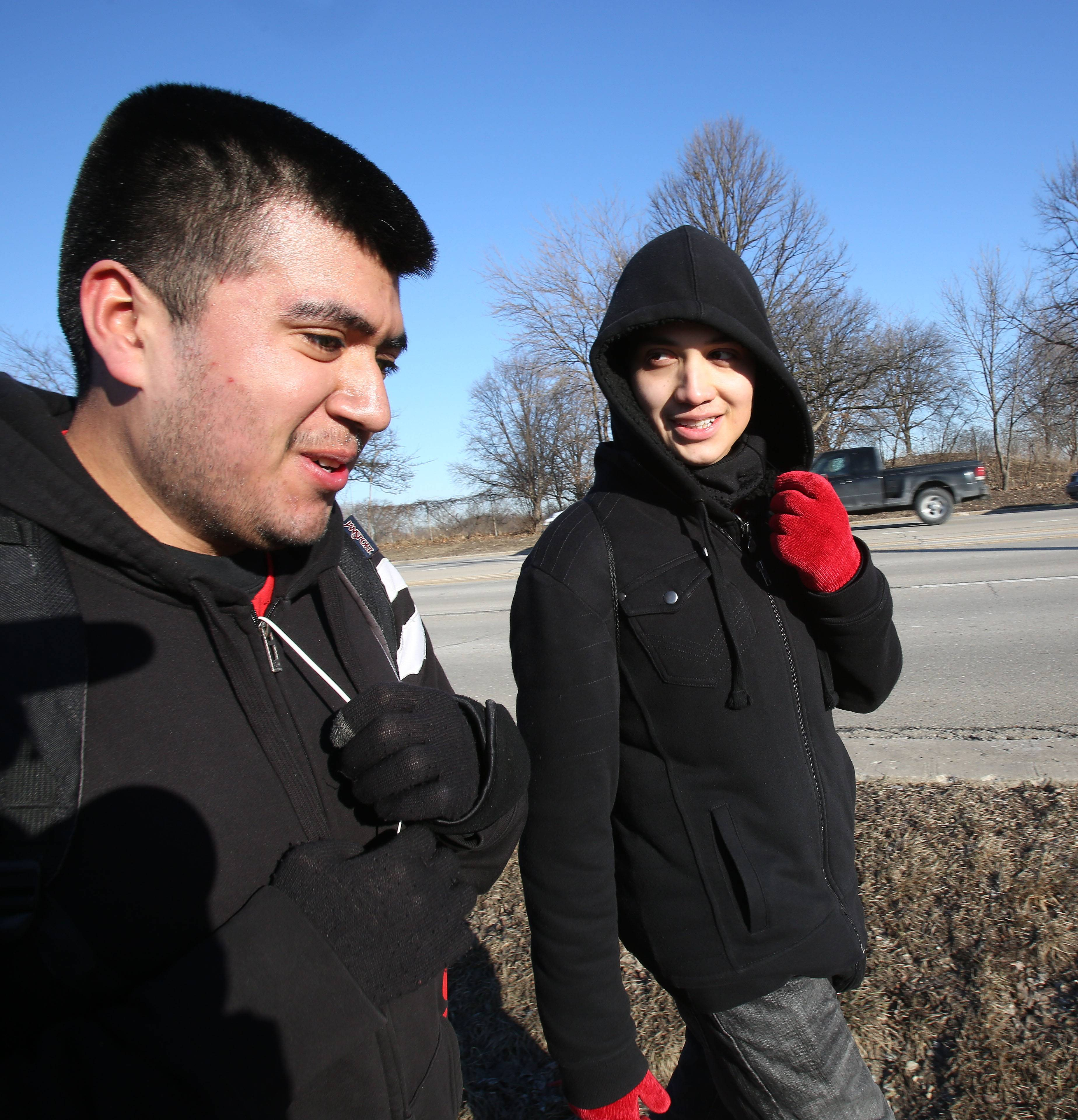 "Edgar Cervantes and Adrian Gallardo, seniors at East Aurora High School, walk Wednesday morning through Naperville as part of the ""Tomcats Journey to Remember,"" a 38-mile walk from their school to Soldier Field in Chicago to raise money to bring a former child soldier to speak in April. Gallardo said he enjoyed the challenge of the 14-hour walk, realizing ""struggling can be one of the most powerful motivating factors in life."""