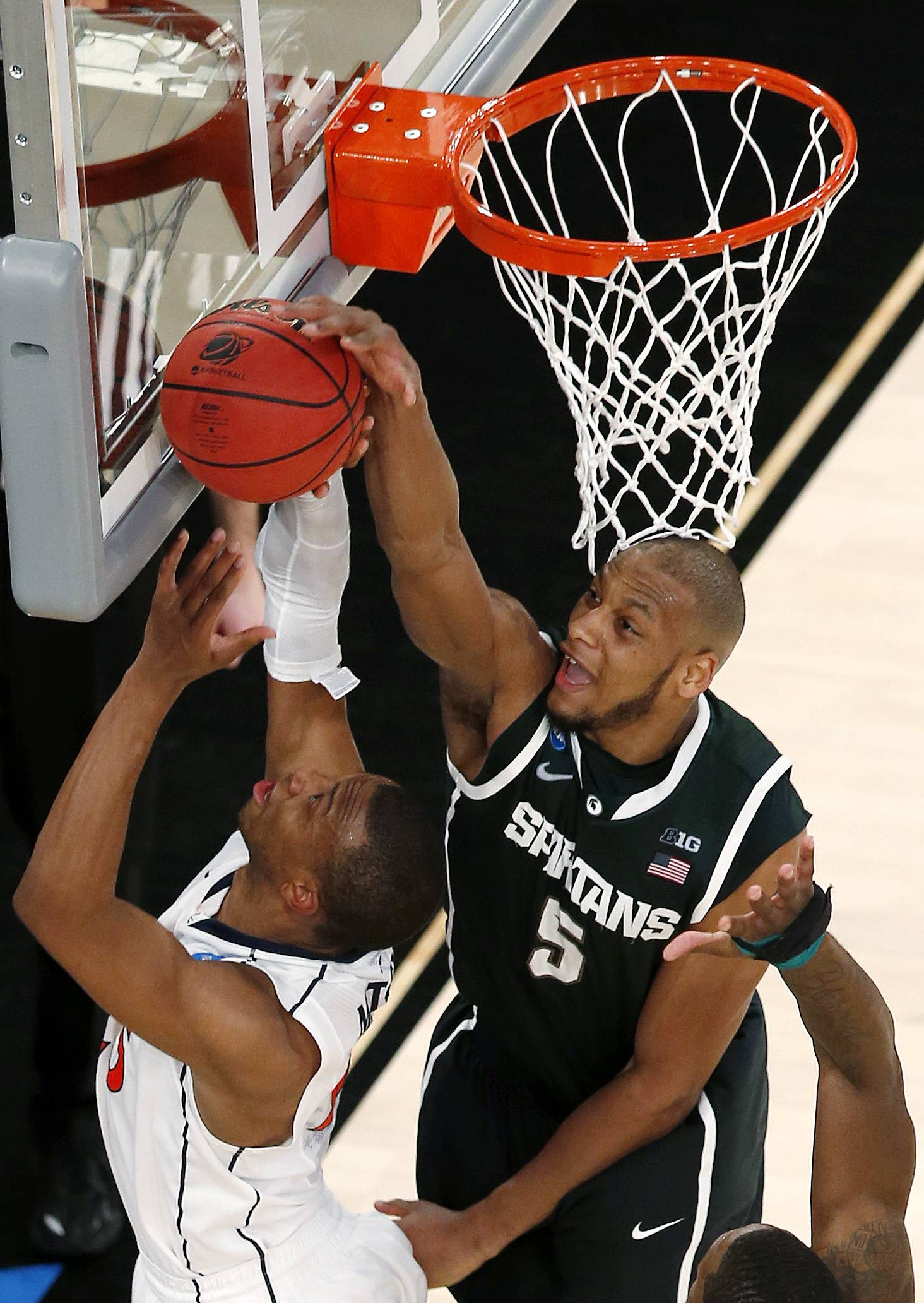 Michigan State forward Adreian Payne, top, blocks a shot by Virginia forward Akil Mitchell during second half of a regional semifinal at the NCAA men's college basketball tournament, early Saturday, March 29, 2014, in New York.