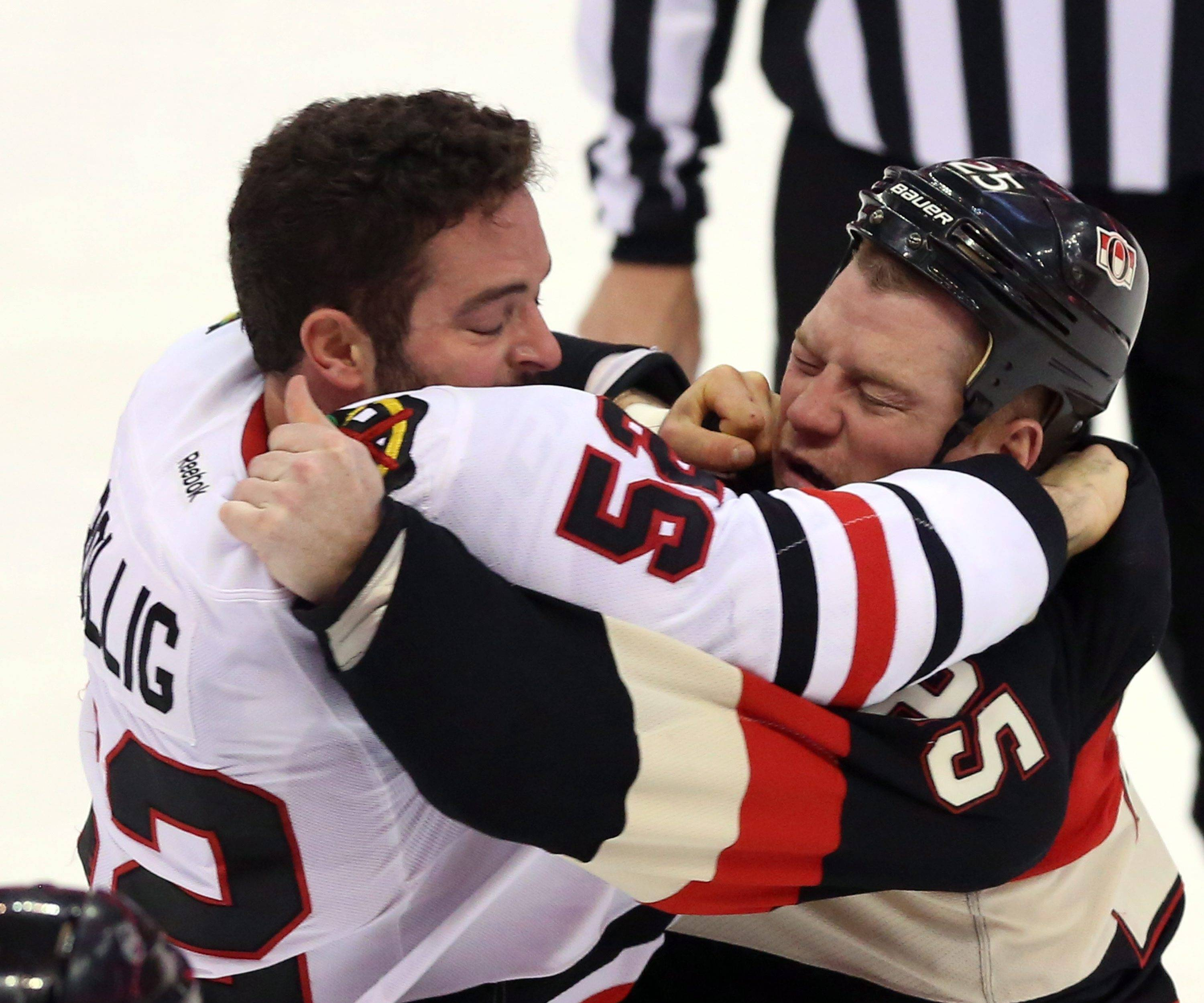 The Blackhawks' Brandon Bollig (52) fights Ottawa Senators' Chris Neil (25) during first-period NHL hockey game action in Ottawa, Ontario, Friday, March 28, 2014.