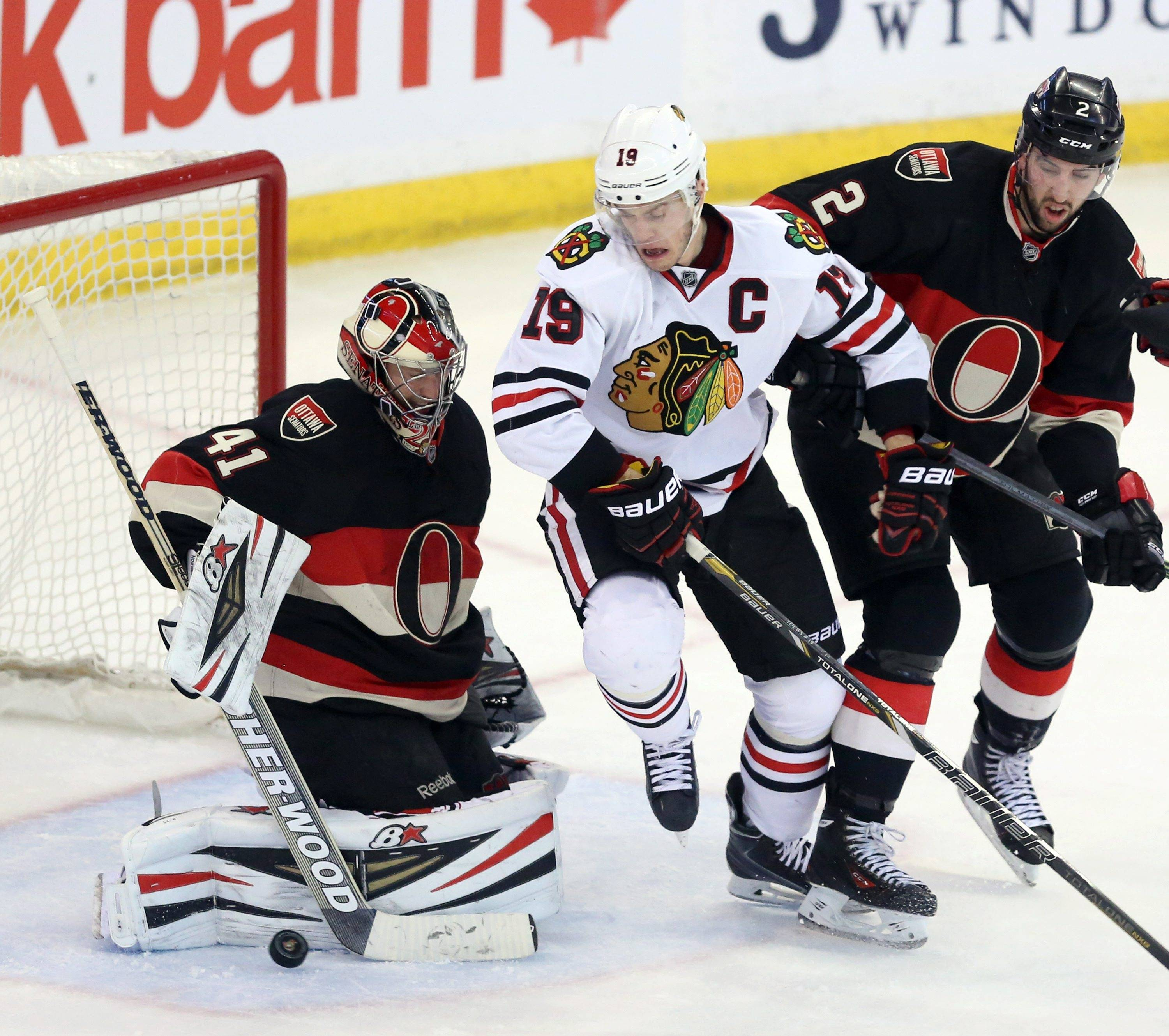 Ottawa Senators goaltender Craig Anderson (41) clears the puck as teammate Jared Cowen (2) and Chicago Blackhawks' Jonathan Toews (19) battle in front of the net during second-period NHL hockey game action in Ottawa, Ontario, Friday, March 28, 2014.