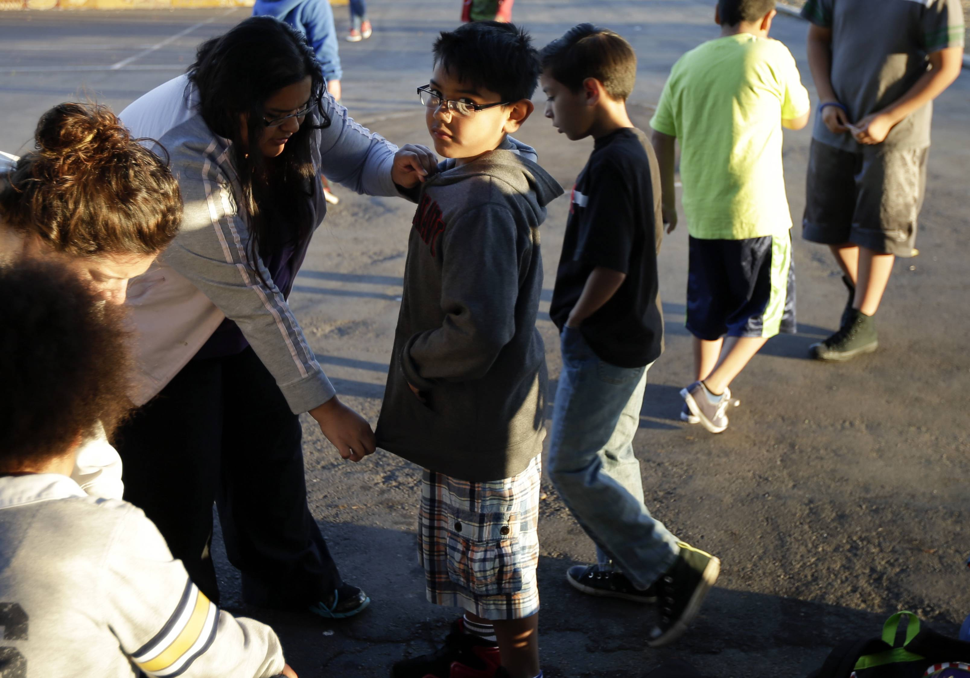Marina Beltran, left, zips up the jacket of her son Antonio before he takes part in an early morning running program at his elementary school in Chula Vista, Calif. Amid alarming national statistics showing an epidemic in childhood obesity, hundreds of thousands of students across the country are being weighed and measured.