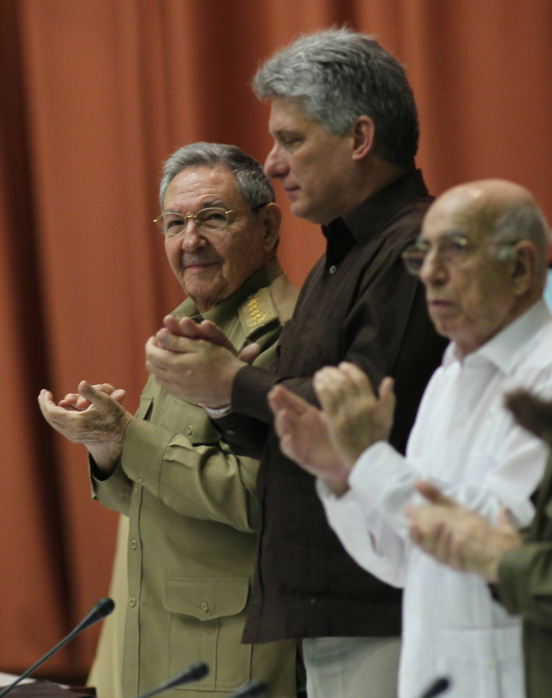 Cuba's President Raul Castro, left, Cuba's Vice President Miguel Diaz-Canel, center, and First Vice-President of the Council of State Jose Ramon Machado Ventura, right, applaud Saturday during an extraordinary session at the National Assembly in a vote that overhauls the foreign investment law in Havana.