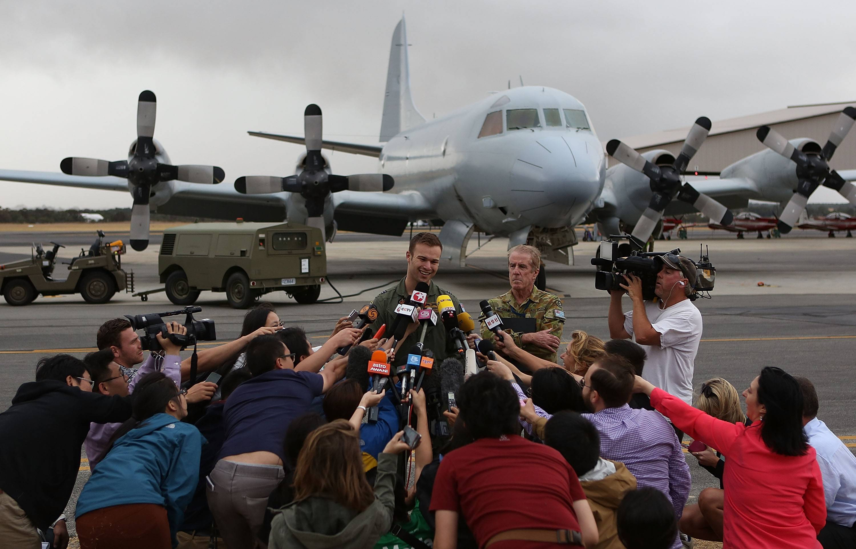 Royal Australian Air Force Flight Lt. Russell Adams speaks to media at Pearce Airbase Saturday, March 29, in Perth, Australia. Five search aircraft yesterday spotted possible debris in the new search area for flight MH370 west of Perth. The Malaysian airliner disappeared on March 8 with 239 passengers and crew on board and is suspected to have crashed into the southern Indian Ocean.