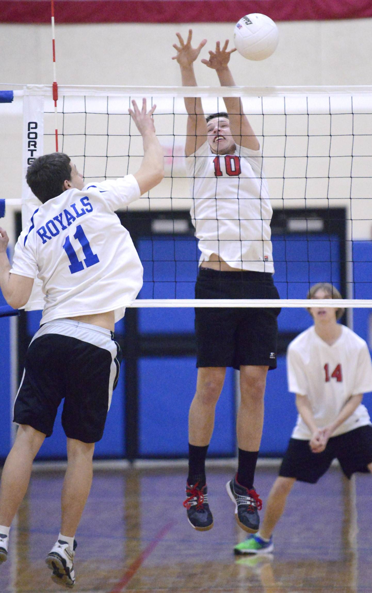 Mundelein's David Everding blocks a spike by Larkin's Dan Horist at Hoffman Estates on Saturday.