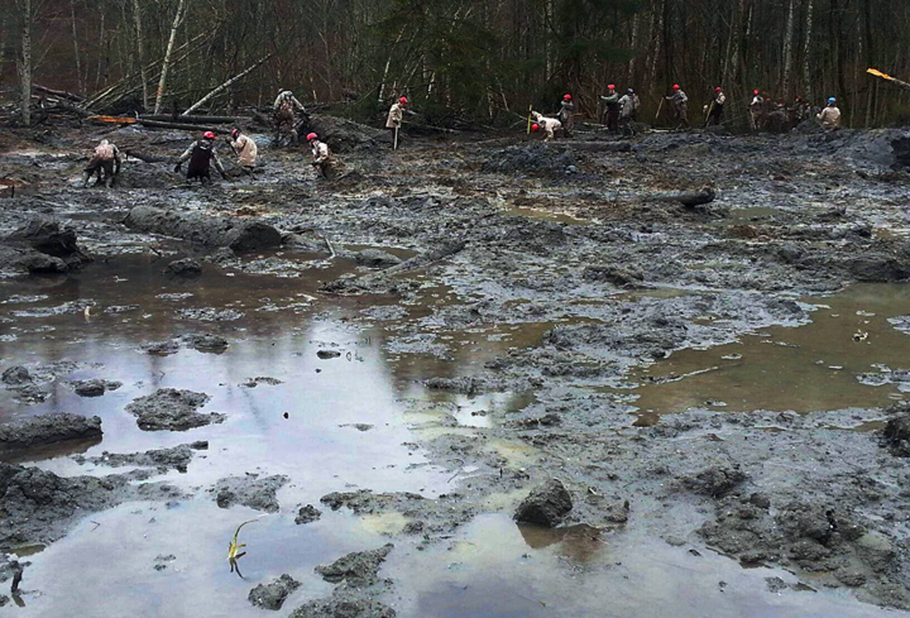 Washington Air National Guardsmen methodically make their way through the mud and wreckage Friday left behind by last Saturday's mudslide near Oso, Wash.