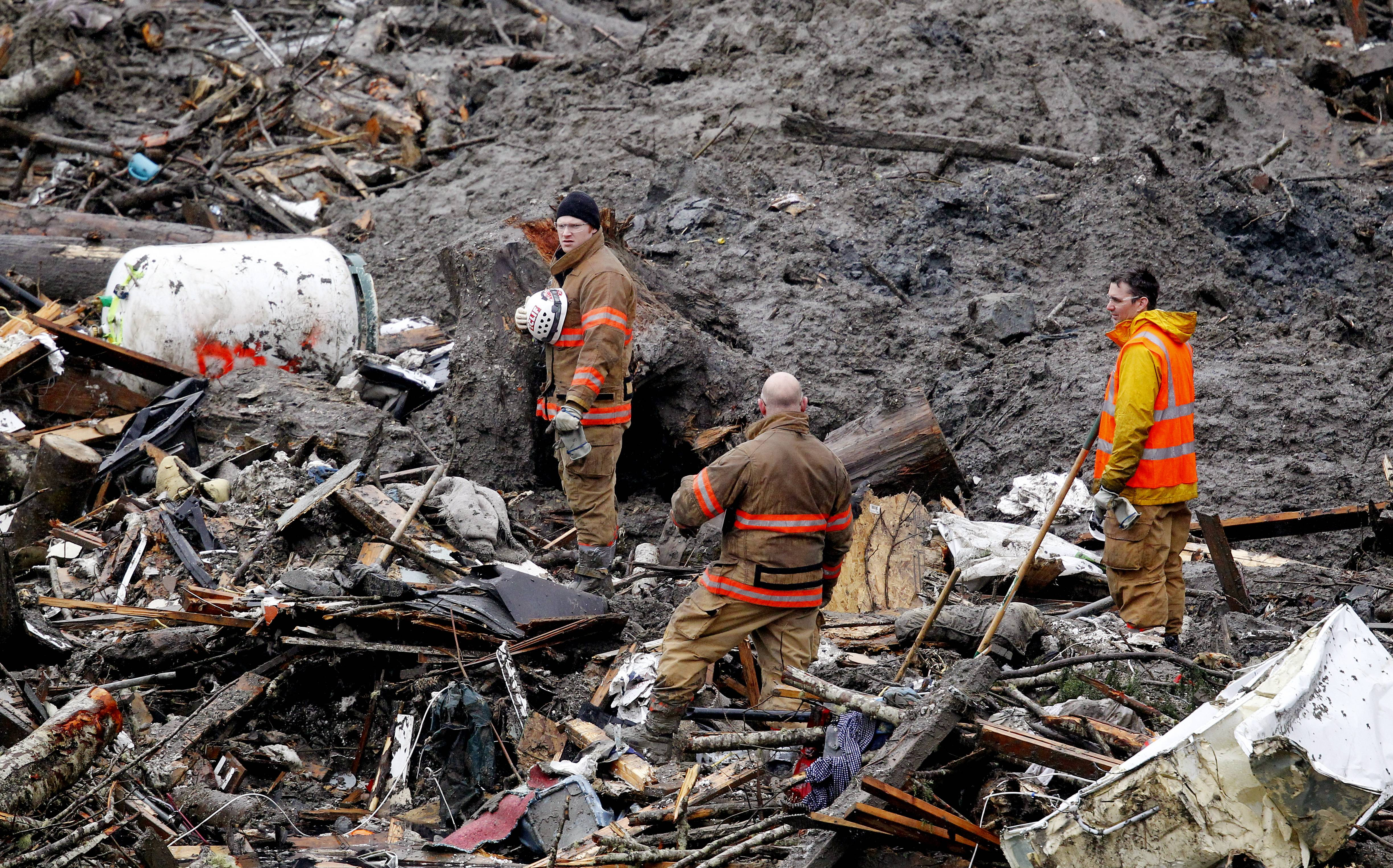 Searchers stand for a moment of silence Saturday at the scene of the  deadly Washington mudslide.