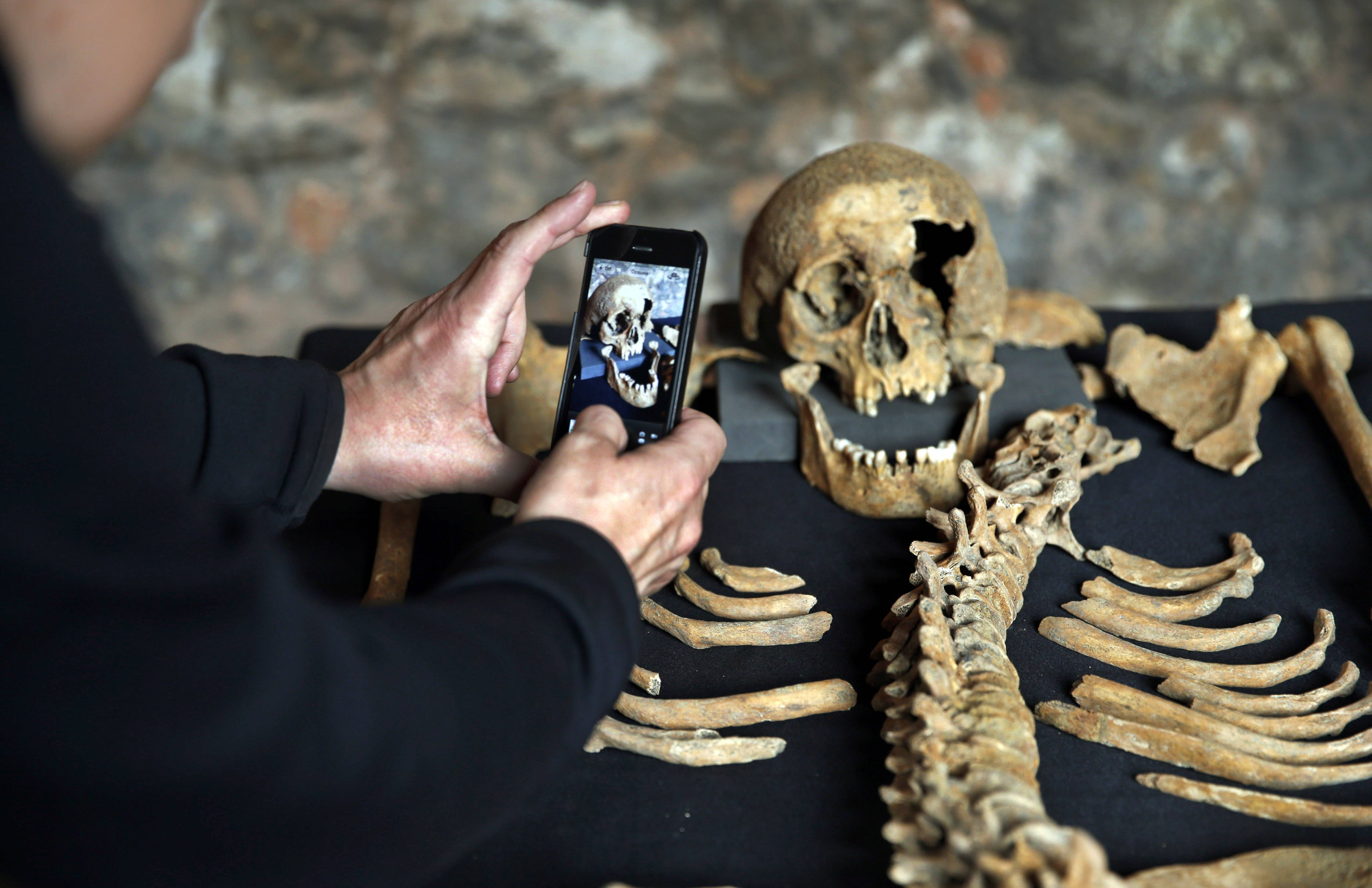 A member of the media photographs the skull Wednesday of one of the skeletons found by construction workers under central London's Charterhouse Square.