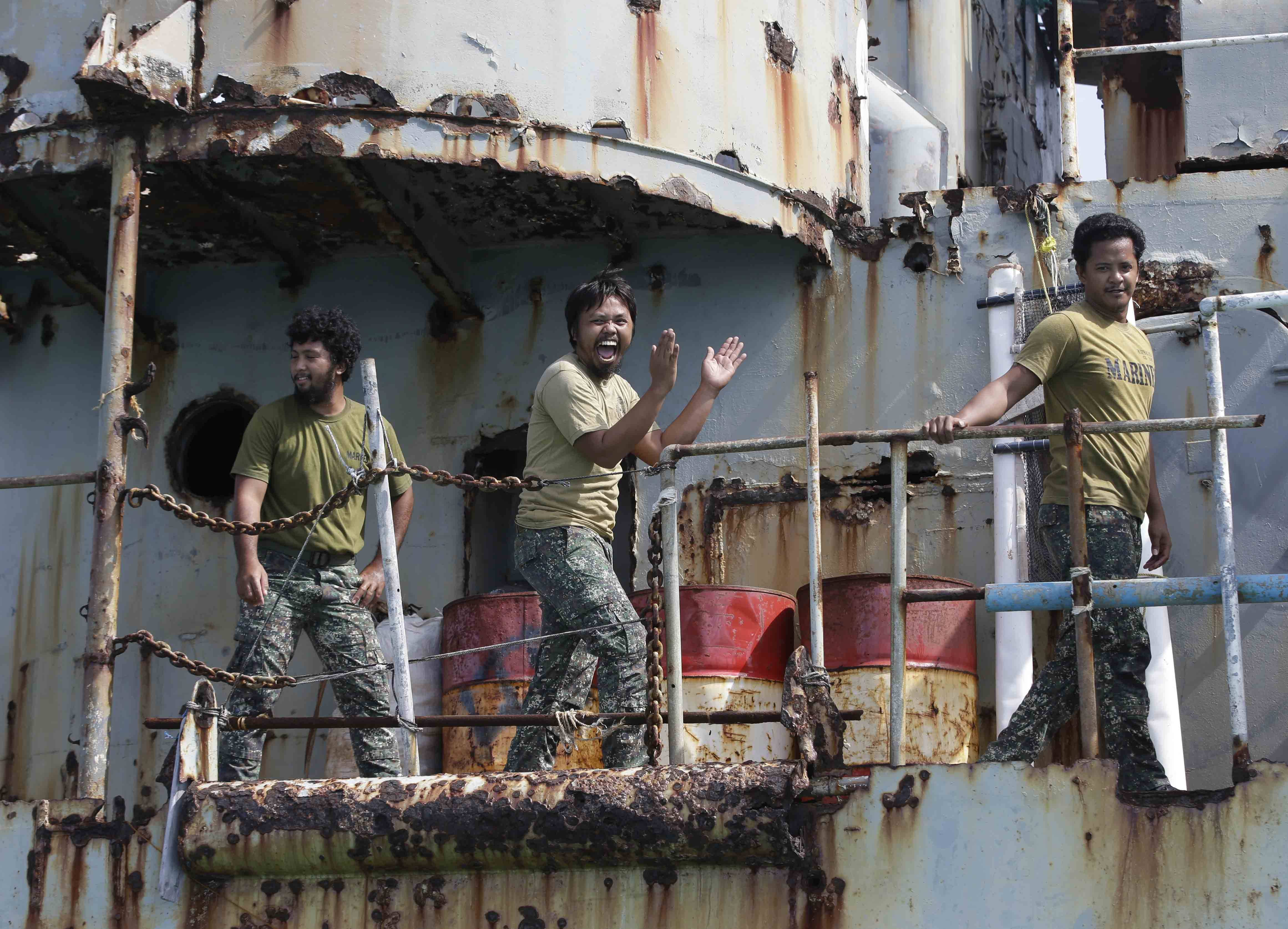 Philippine Marines deployed on the Philippine Navy ship LT 57 Sieera Madre applaud after the Philippine Government vessel AM700 successfully docks beside it off Second Thomas Shoal.