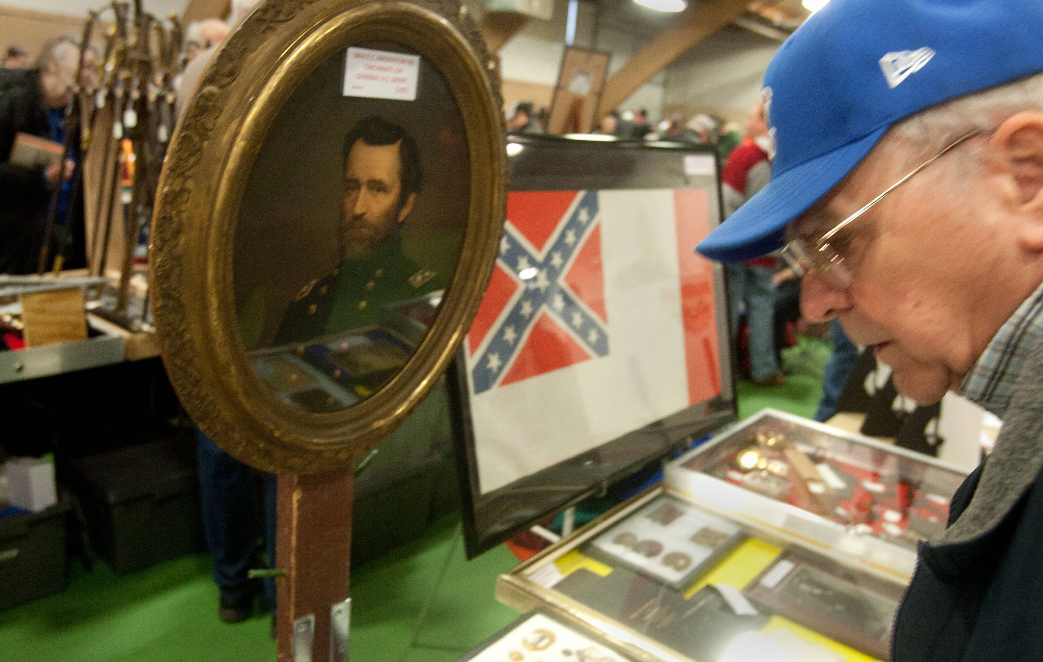 Ron Bellenger of Holland, Mich., looks over items on display at the Chicagoland National Civil War and Military Extravaganza at the DuPage County Fairgrounds. A Middleton oil painting of Gen. Ulysses S. Grant stands next to the third pattern of the Confederate national flag.