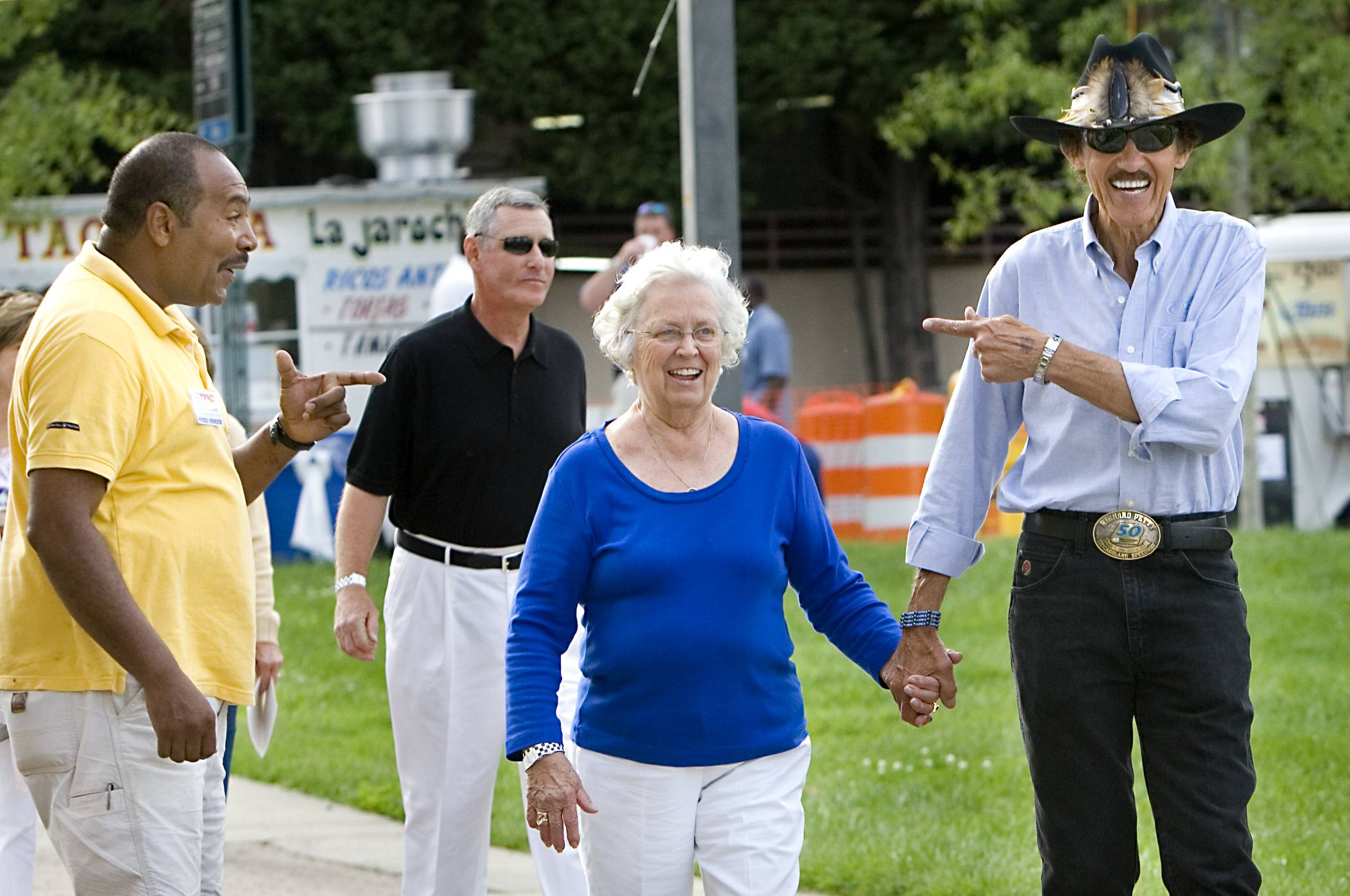 NASCAR Hall of Famer driver Richard Petty, holding the hand of his wife Lynda center, are recognized by fans in Greensboro, N.C. Lynda Petty  died Tuesday.