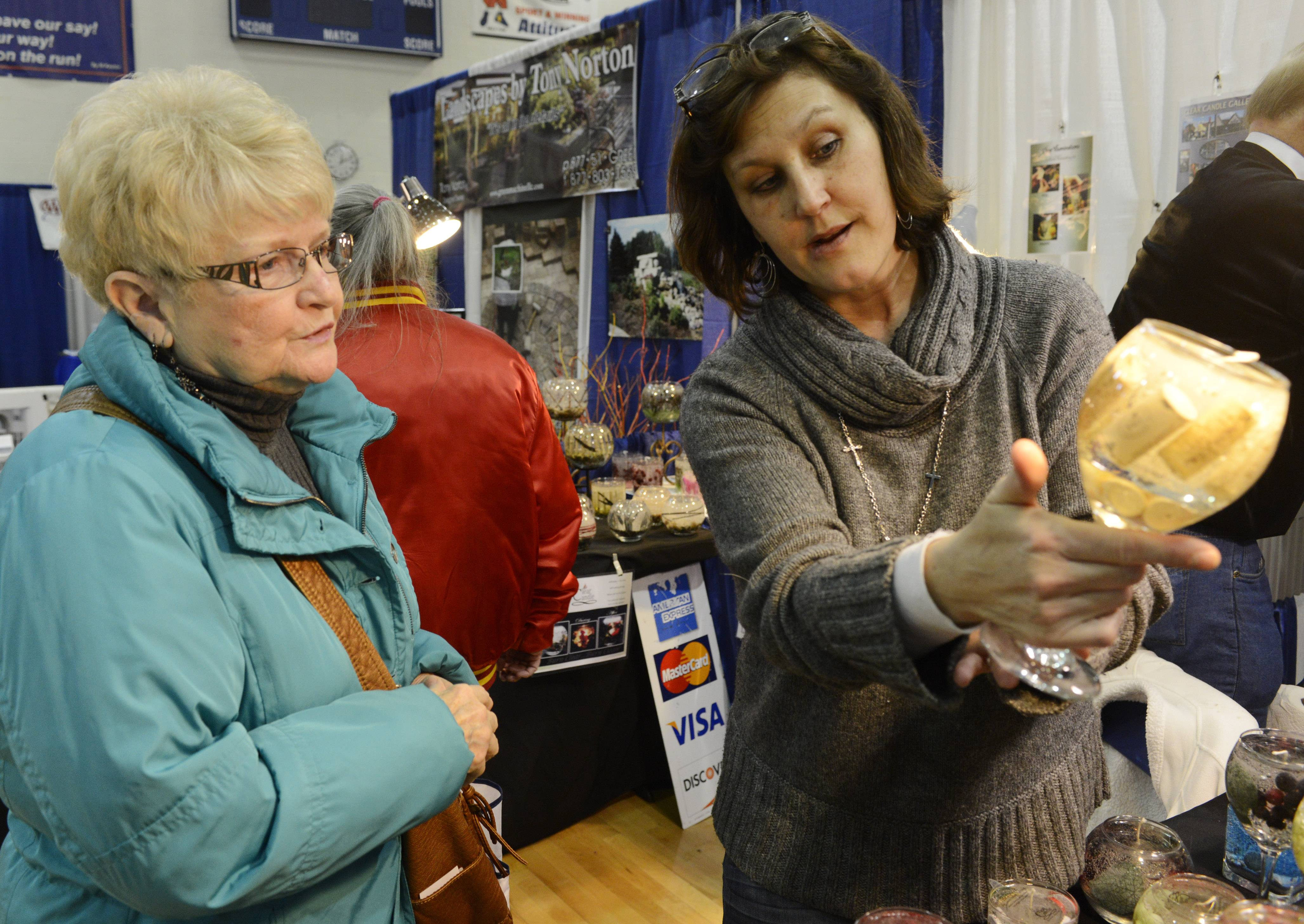Melba Ingoglia of Fox Lake views an item held by sales associate Diane Sineni of Clear Candles, Arlington Heights, Saturday during the Springfest Expo 2014, held by the Lindenhurst-Lake Villa Chamber of Commerce at Lakes Community High School.