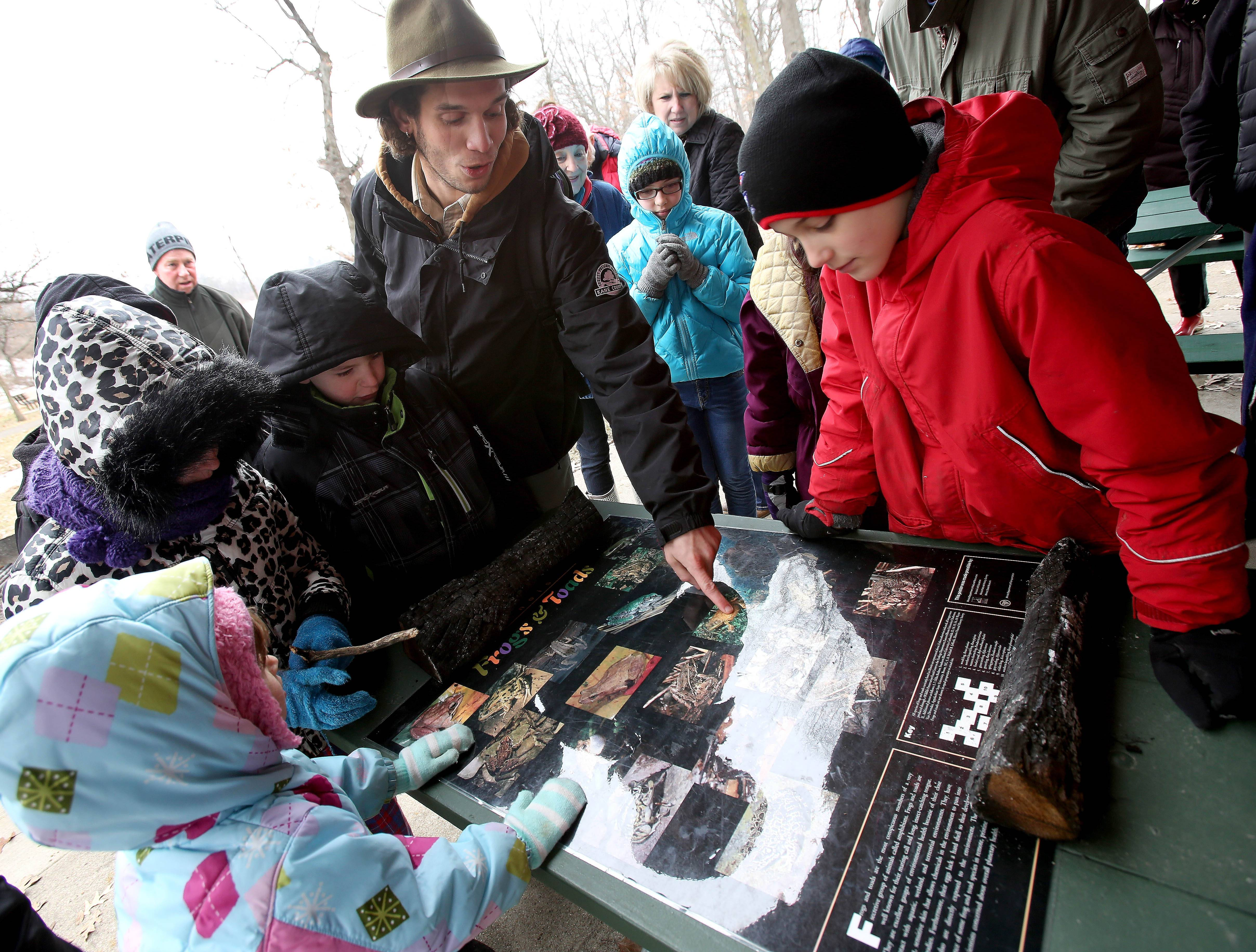 "Tyler Bouchard, 9, right, of Carpentersville and other kids take a look as naturalist Josh Libman points out a type of frog during a program called ""Fabulous Frogs"" on Saturday, March 29, at Burnidge Forest Preserve in Elgin. Due to the cold temperatures, frogs were still dormant."