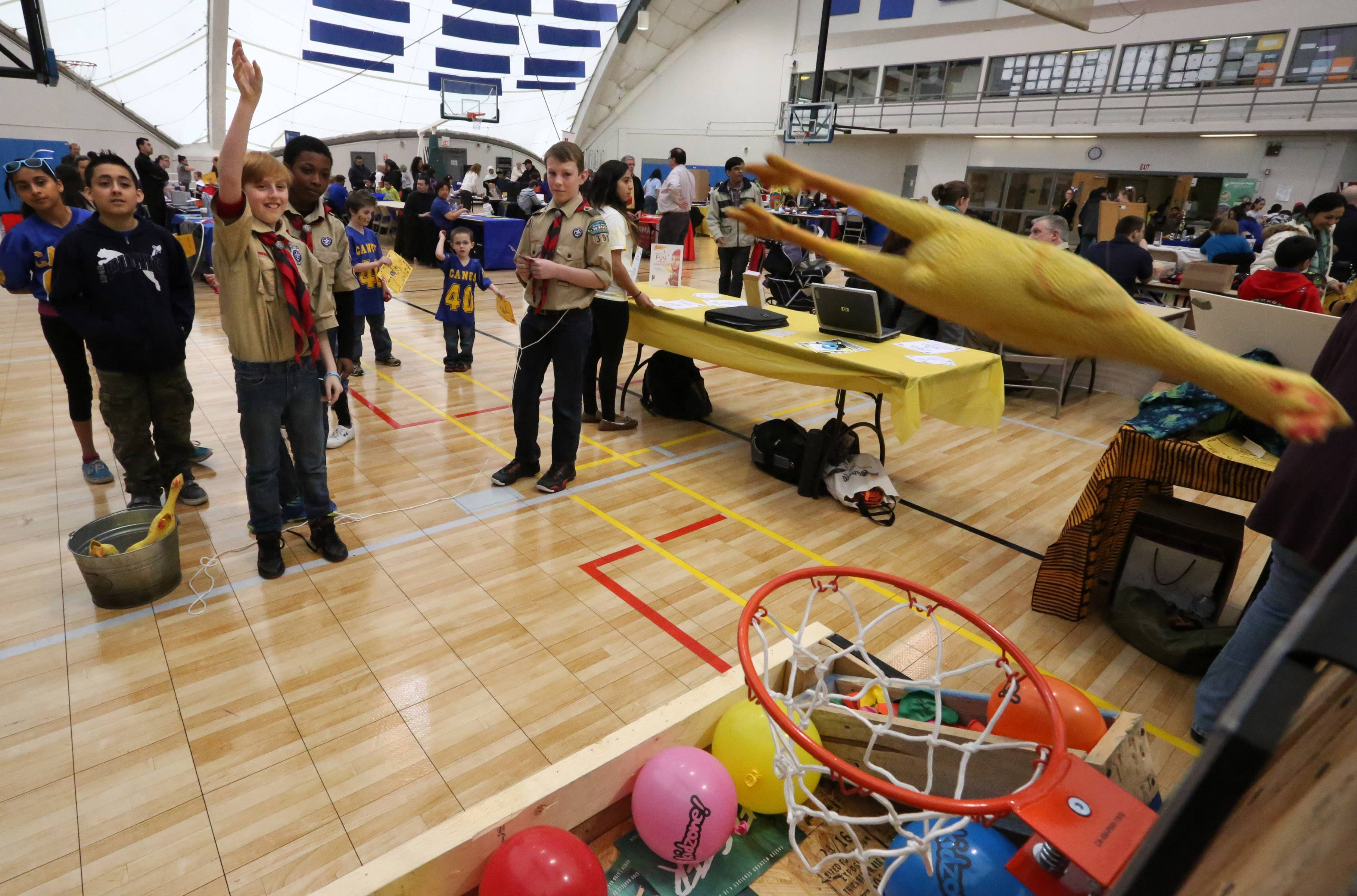 Shawn Prigge, 11, of Hanover Park, with Boy Scouts Troop 398, tosses a rubber chicken towards a basketball hoop at the Kids at Hope Community Resource Fair at Hanover Park's Community Center Gym on Saturday.
