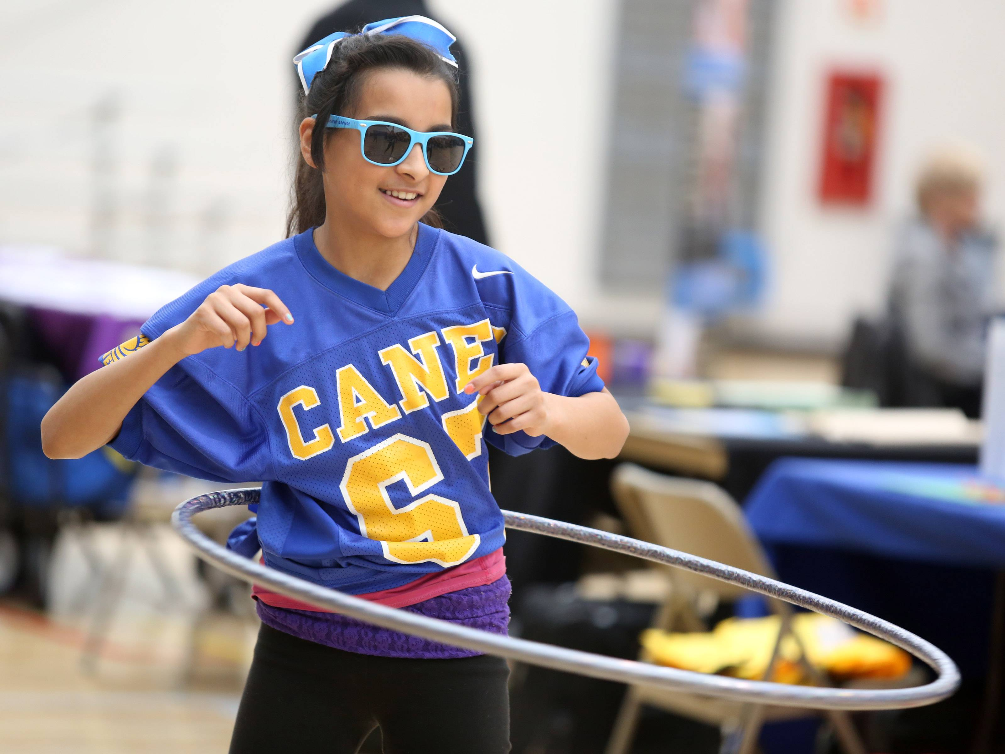 Roxanna Perez, 11, of Hanover Park participates in a hula-hoop contest at the Kids at Hope Community Resource Fair at Hanover Park's Community Center Gym on Saturday.