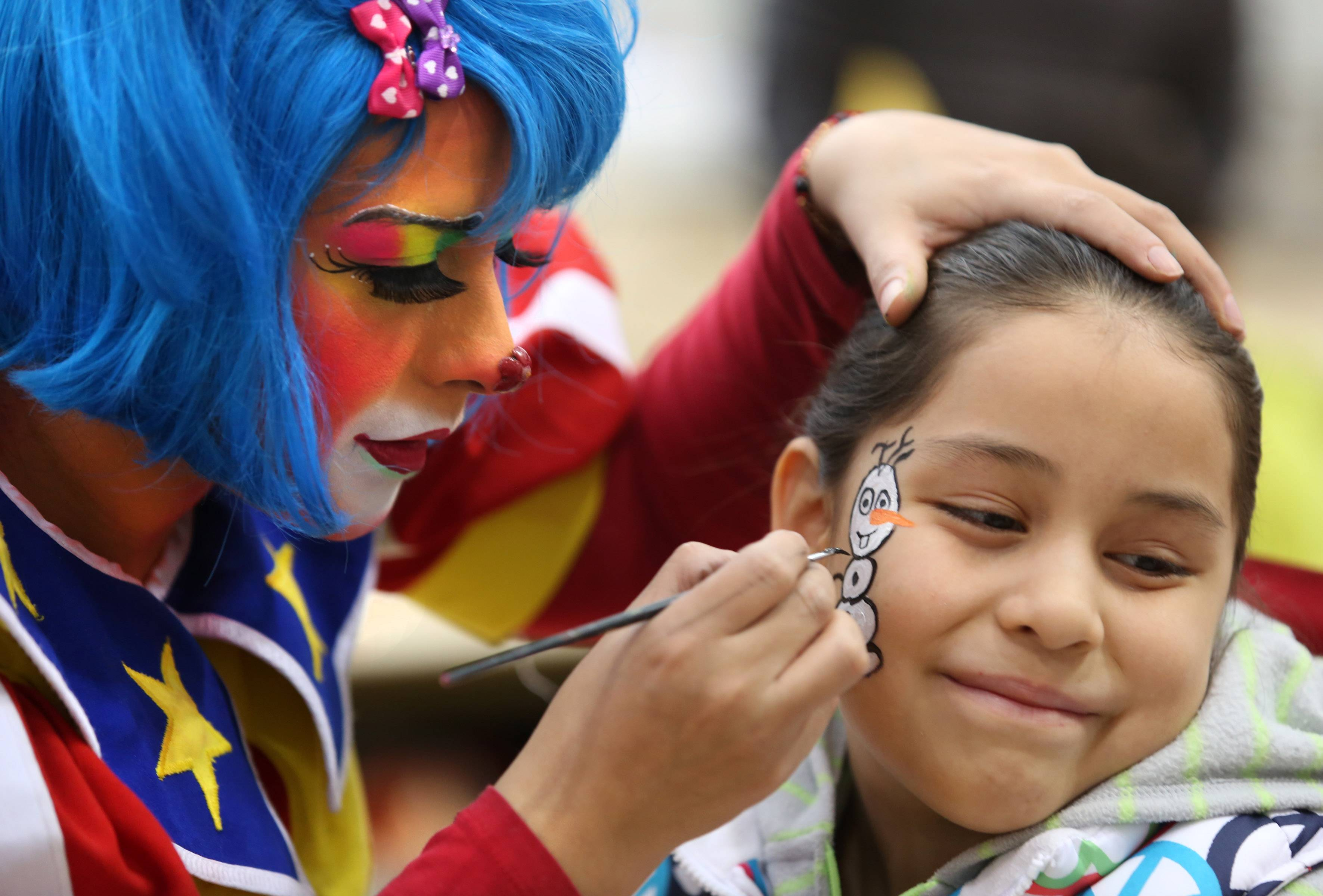 Montse Acosta, 9, gets a snowman painted on her face by Ruth Flores playing the role of Chispita the Clown, both of Hanover Park, at the Kids at Hope Community Resource Fair at Hanover Park's Community Center Gym on Saturday.