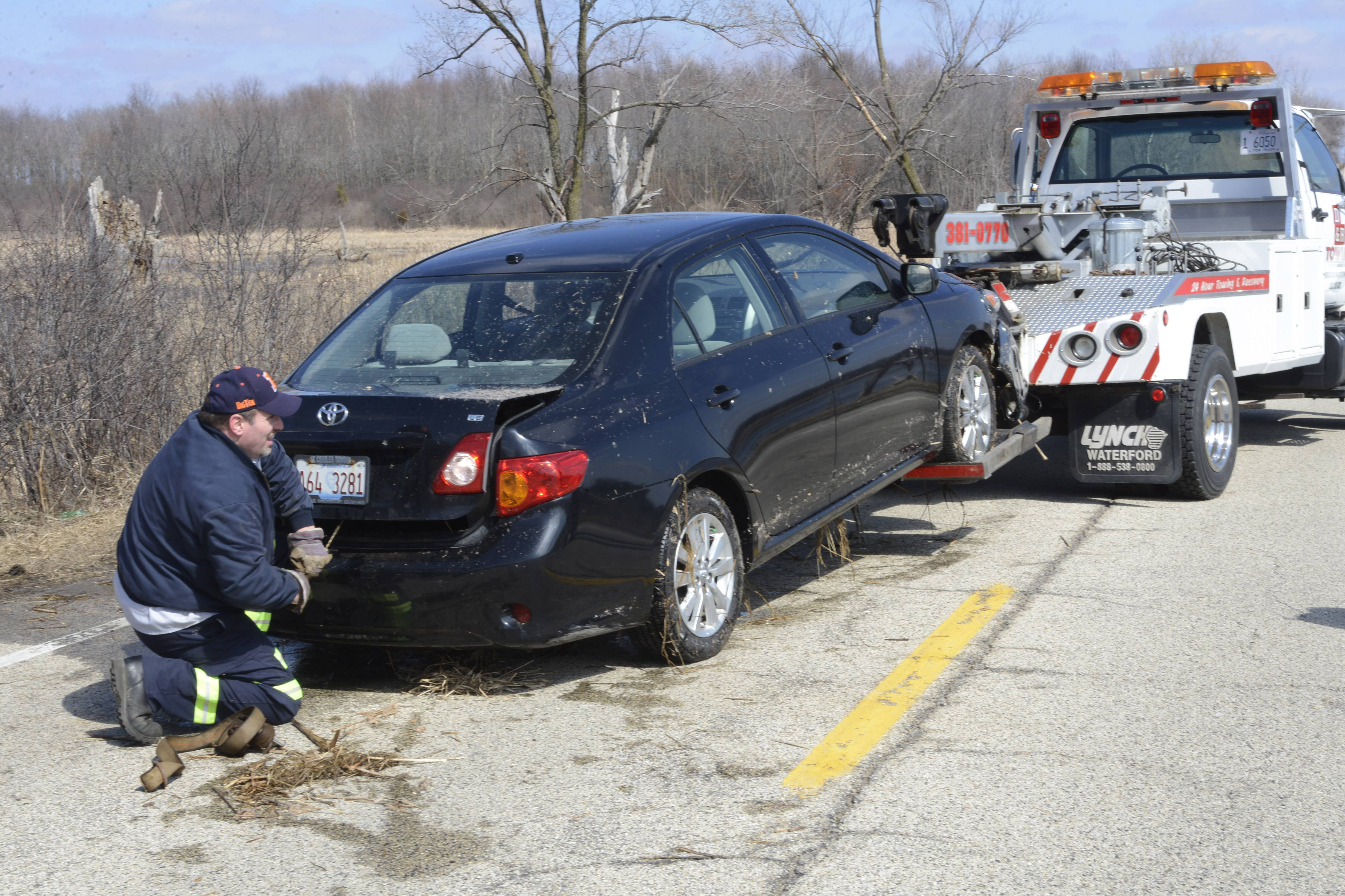 A Toyota Corolla, which veered from Palatine Road and came to a rest in about 3 feet of water in a wetlands, is towed from the scene in Barrington Hills Saturday. The female driver and a 3-year-old girl were not injured.