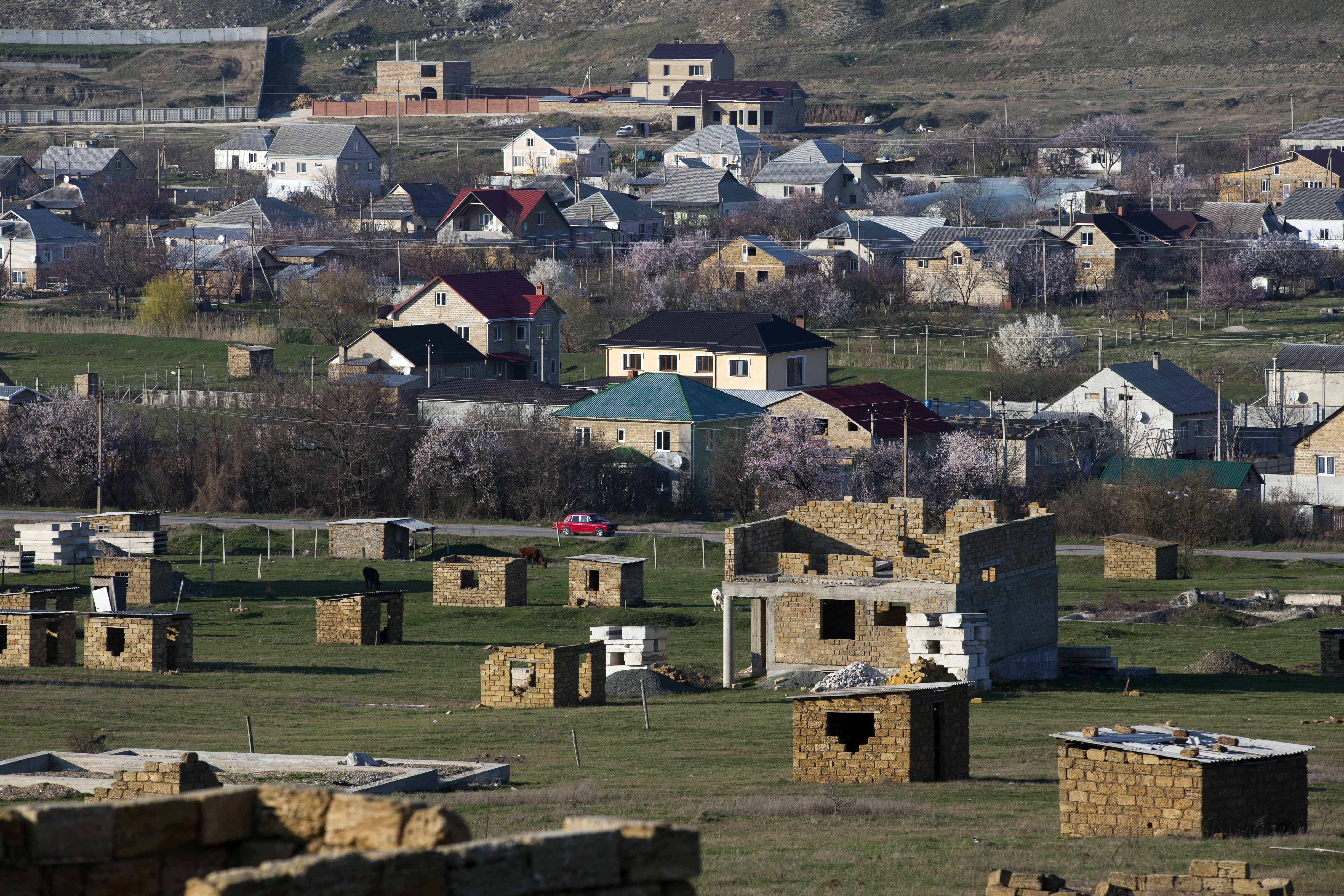 A car passes between Crimea's Tatars recent and long-standing squatter settlements, foreground, in the village Lozovoye-2, not far from Simferopol, Crimea.