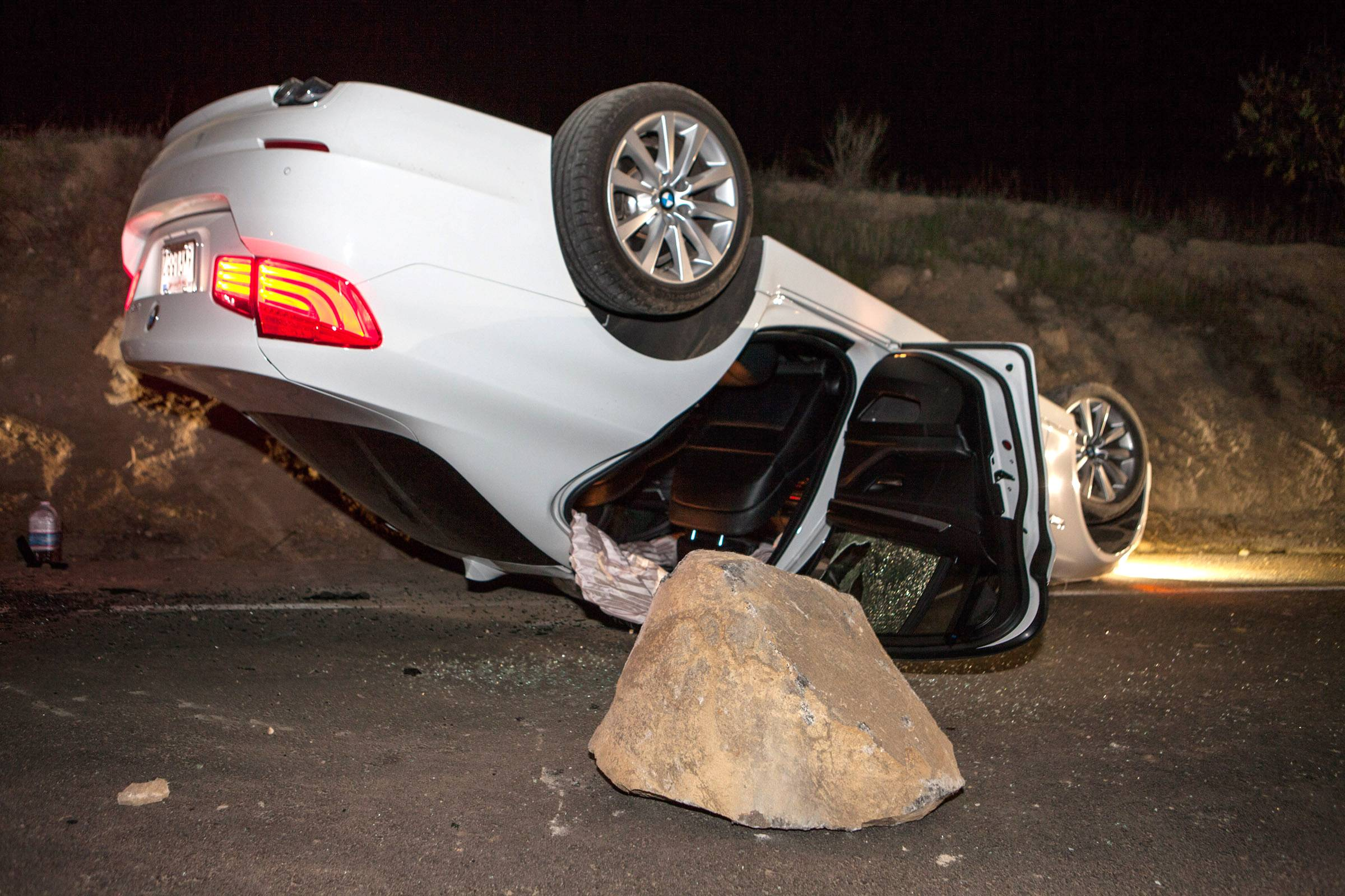 A car sits overturned on a highway in the Carbon Canyon area of Brea, Calif., Friday night, March 28, after hitting a rock slide caused by an earthquake. The people inside the car sustained minor injuries. A magnitude-5.1 earthquake centered in the area near Los Angeles caused no major damage but jittered nerves throughout the region as dozens of aftershocks struck into the night.