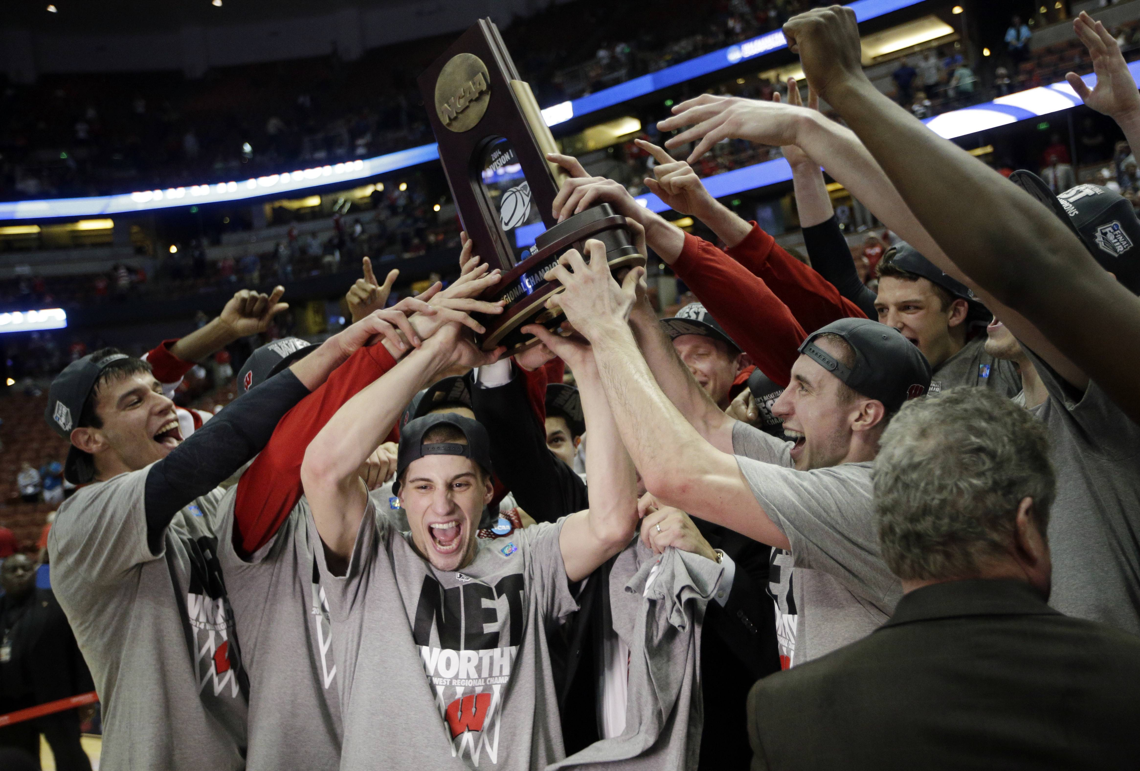 Wisconsin players celebrate after they won their regional final NCAA college basketball tournament game against Arizona, Saturday in Anaheim, Calif.
