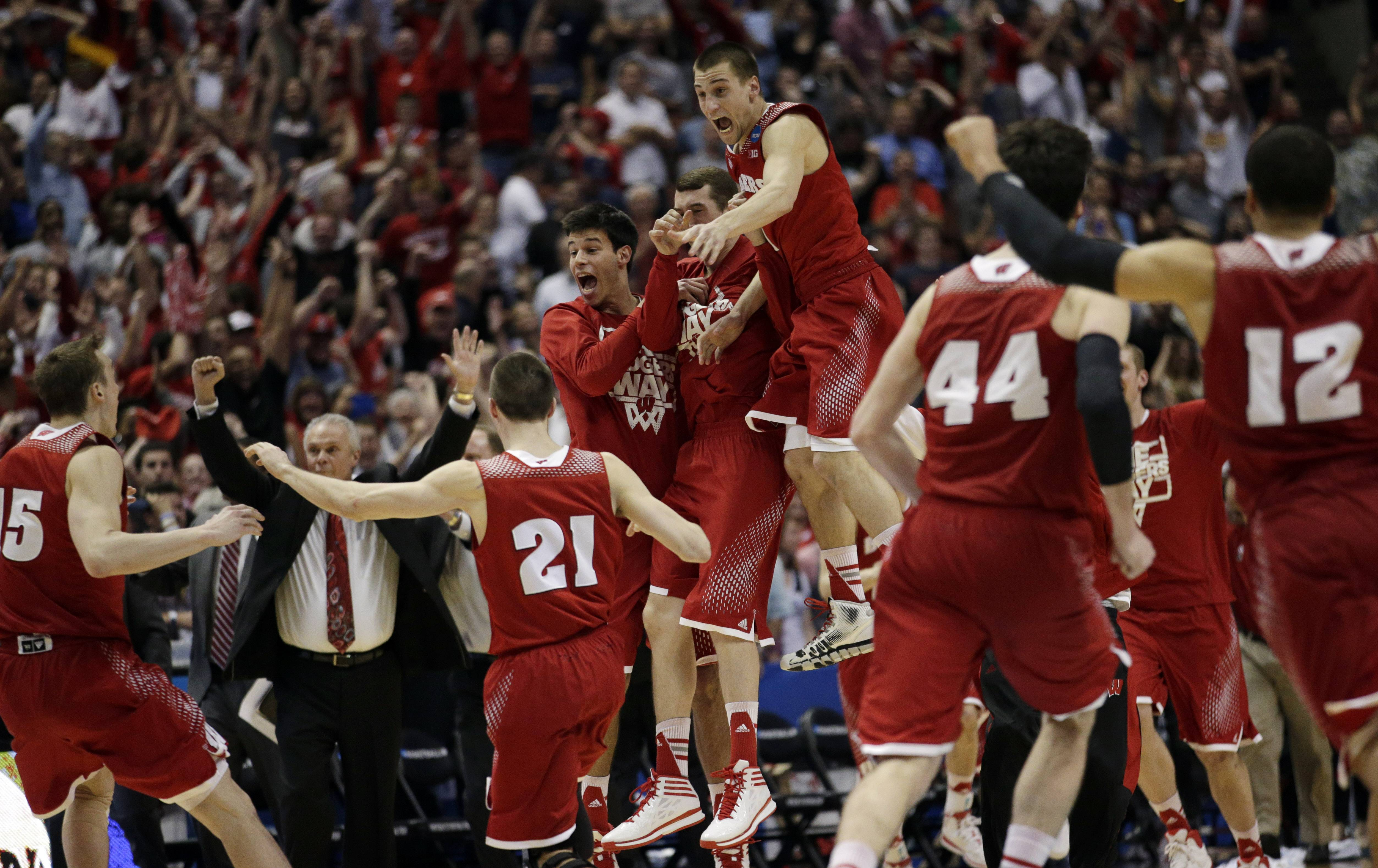 Wisconsin players react as time runs out in overtime in their regional final NCAA college basketball tournament game.