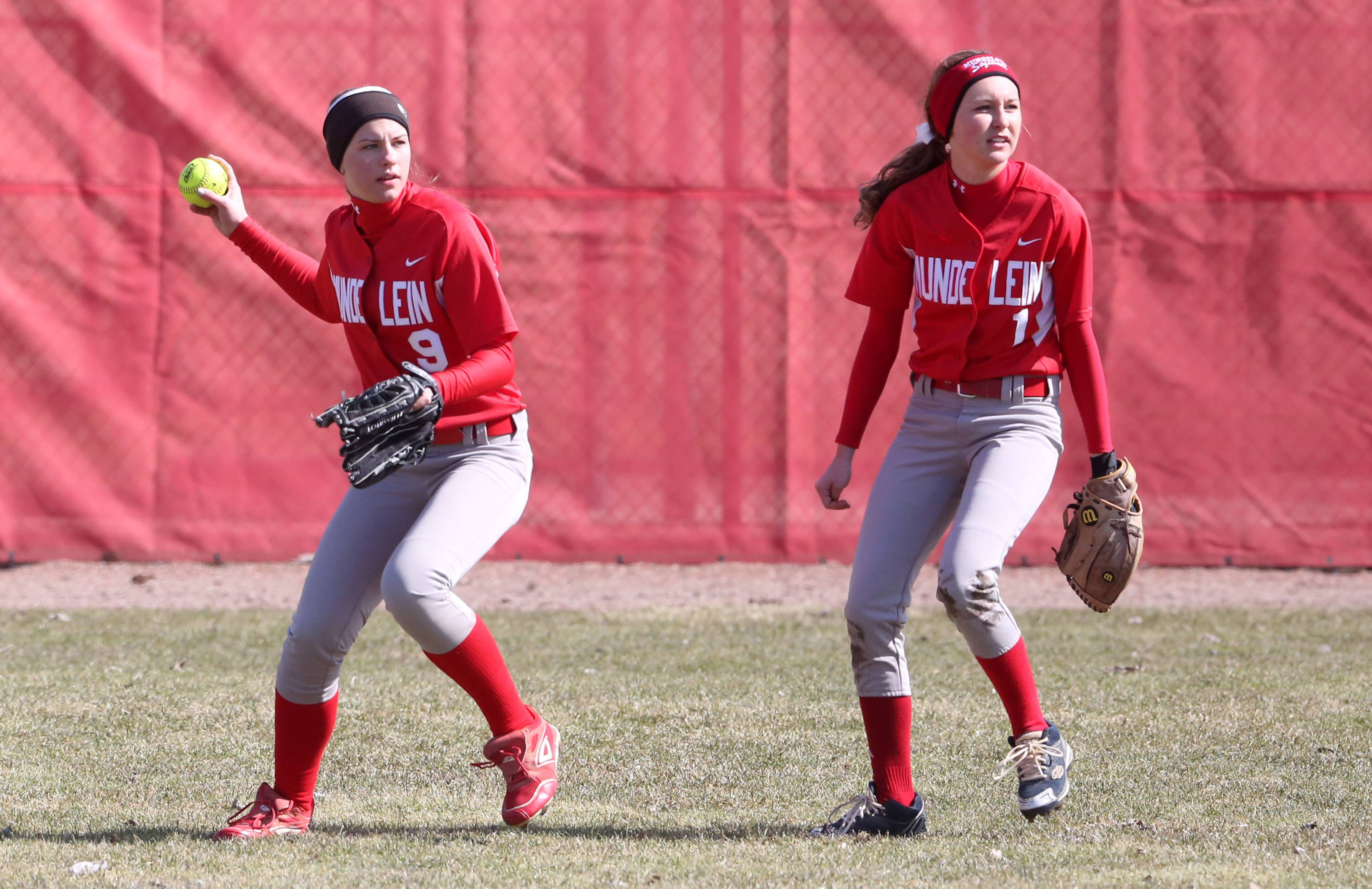 Mundelein center fielder Karlee Bussche throws to second base with left fielder Danielle Beelow watching runners against Elk Grove at the Fields of Dreams on Saturday in Barrington.