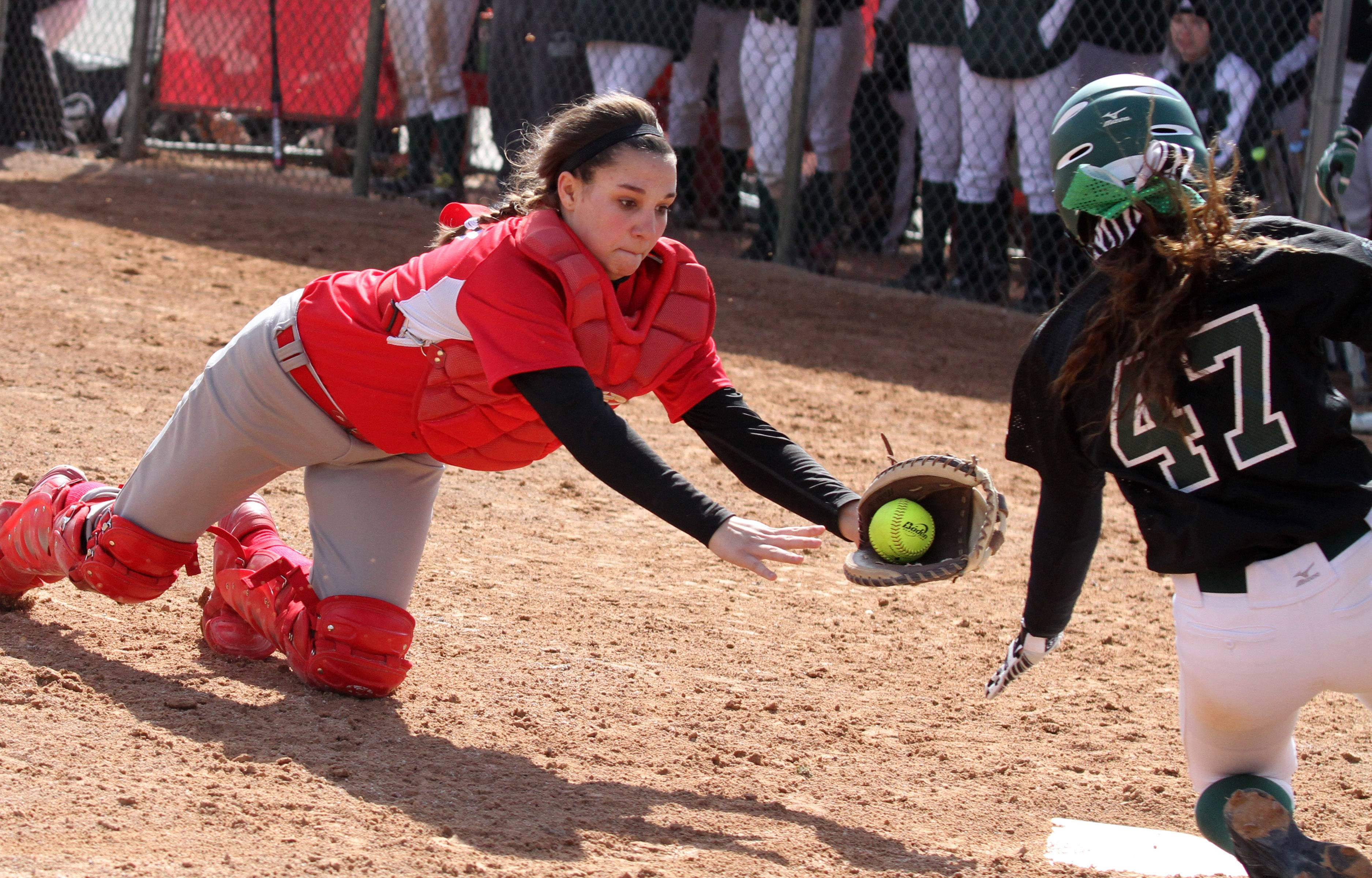 Mundelein catcher Maggie Mahar reaches for Elk Grove's Aleece Duffy as she slides into home plate safely at the Fields of Dreams on Saturday in Barrington.