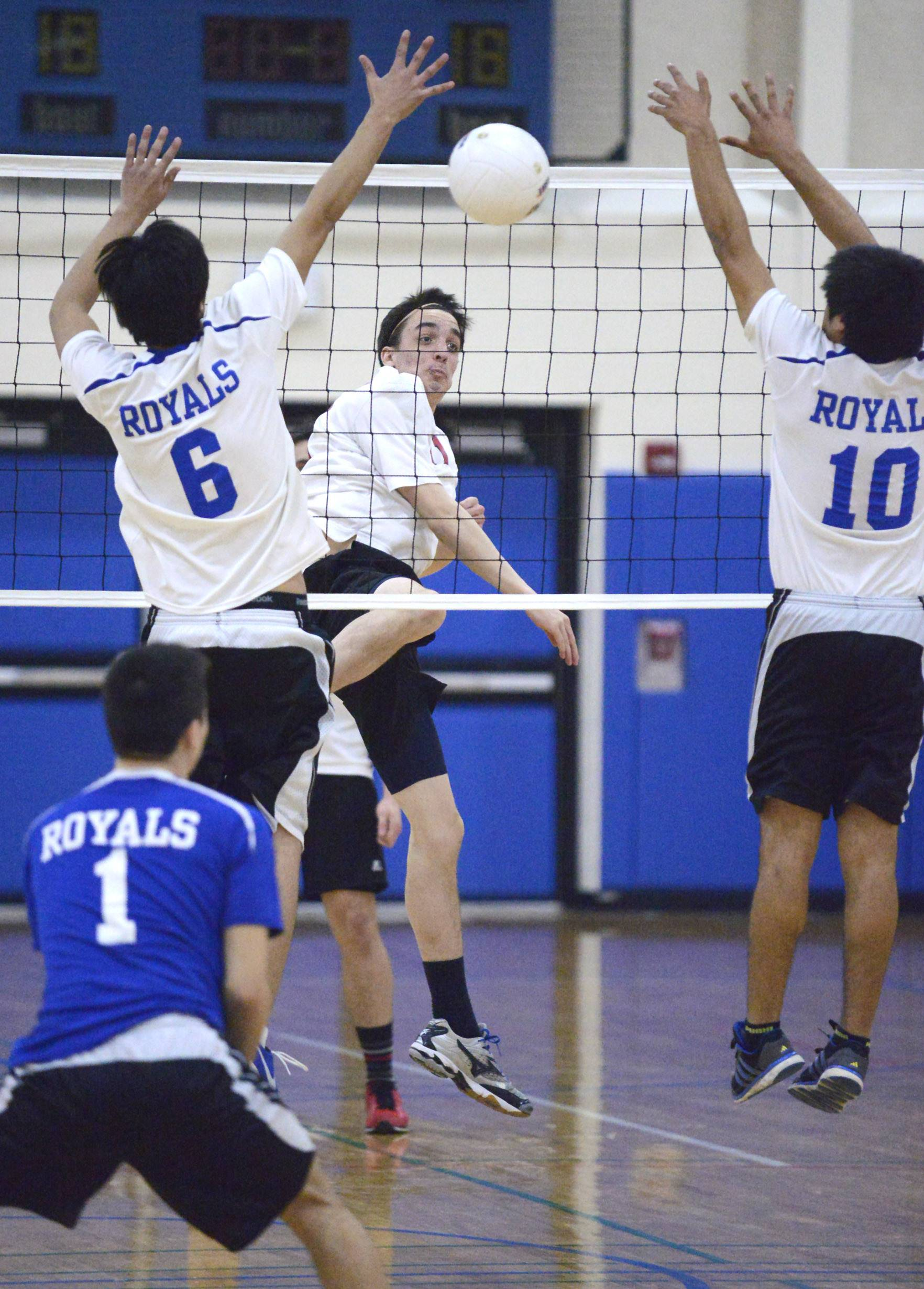 Larkin's Victor Rosas and Rodrigo Tapia attempt to block a spike by Mundelein's Luke Ramer at Hoffman Estates on Saturday.