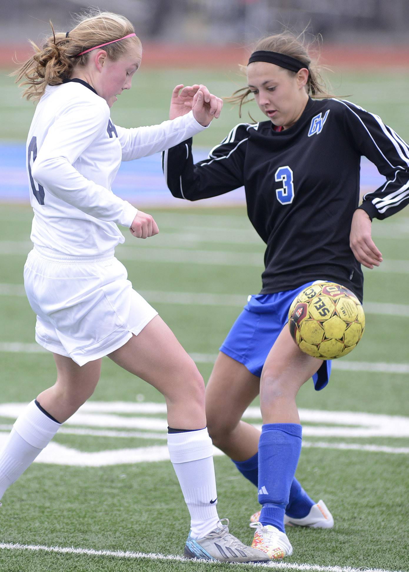 West Aurora's Taylor Truckenbrod, left, and Geneva's Megan Fitz fight for the ball in the first half in Aurora on Saturday, March 29.