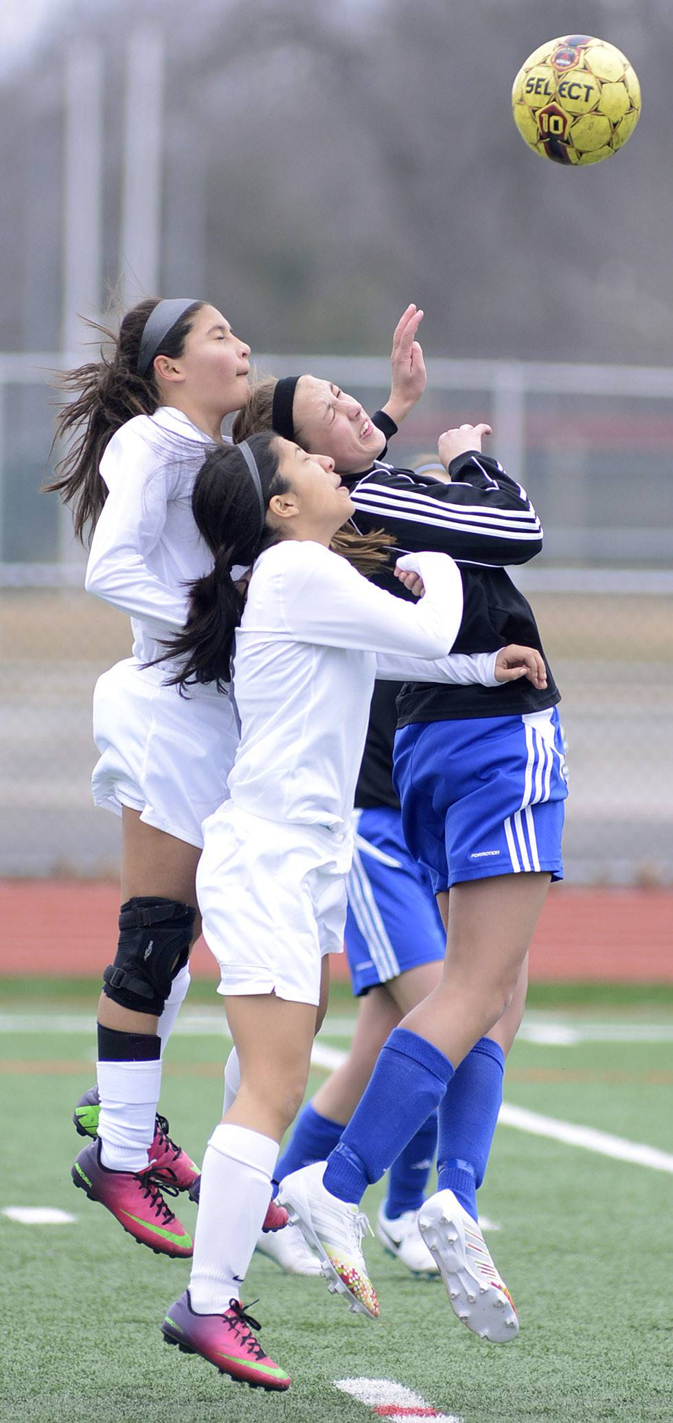 West Aurora's Jocelyn Ferrar (left) and Cristina Sosa (center) and Geneva's Megan Fitz leap in tandem for a header.